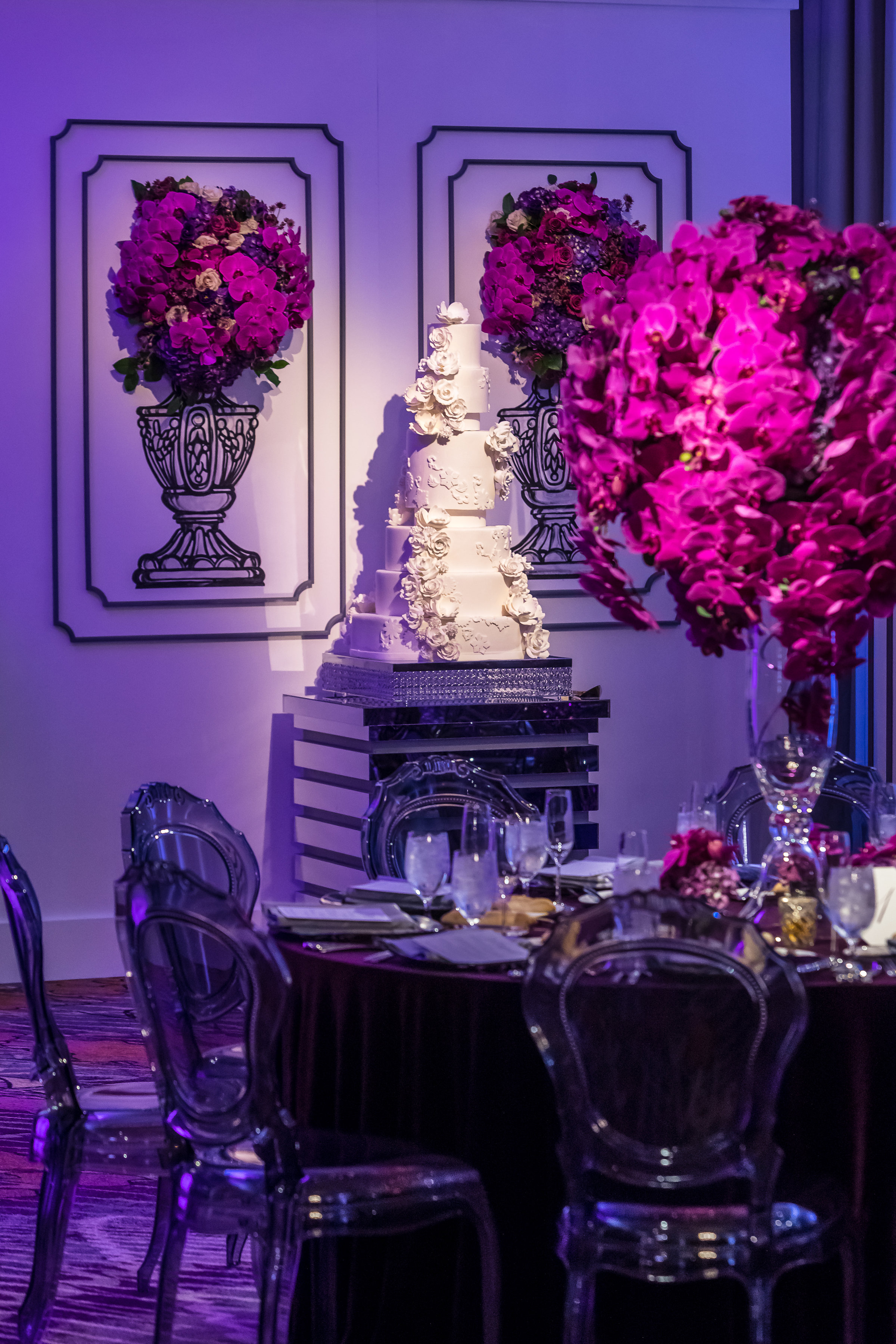 White on white wedding cake in a purple wedding reception.    Wedding Planner: Andrea Eppolito Events  | Photography  Brian Leahy  | Venue & Catering: Mandarin Oriental / Waldorf Astoria | Floral & Decor: Destinations by Design  | Lighting: LED Unplugged   | Hair & Make Up: Amelia C & Co