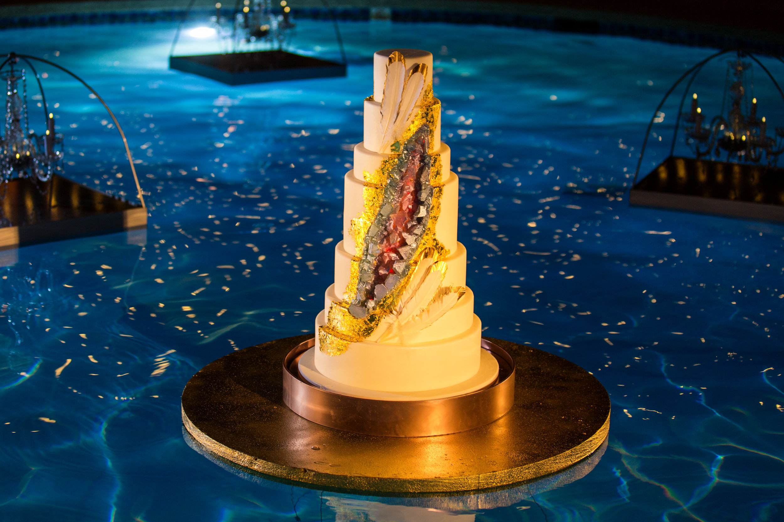 Floating wedding cake with geode and gold tipped feathers. Las Vegas Wedding Planner Andrea Eppolito. Wedding Cake by Four Seasons Las Vegas. Photo by AltF.