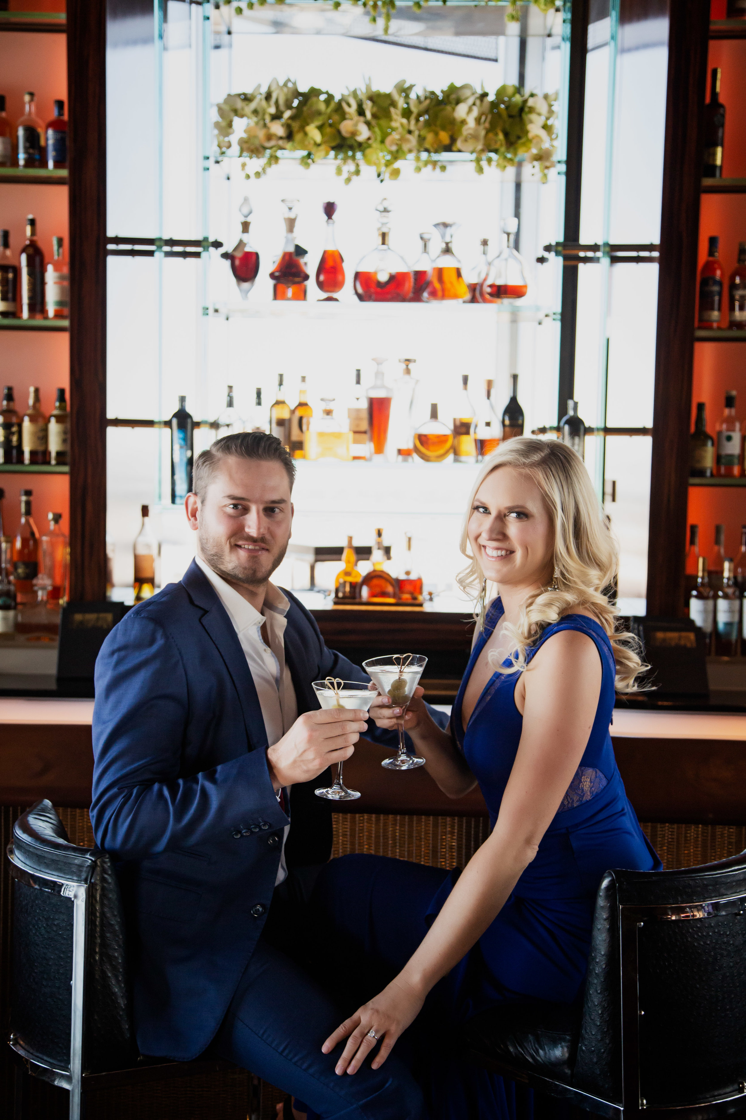 Bride and groom in blue for engagement photos taken in bar at Waldorf Astoria. www.andreaeppolitoevents.com