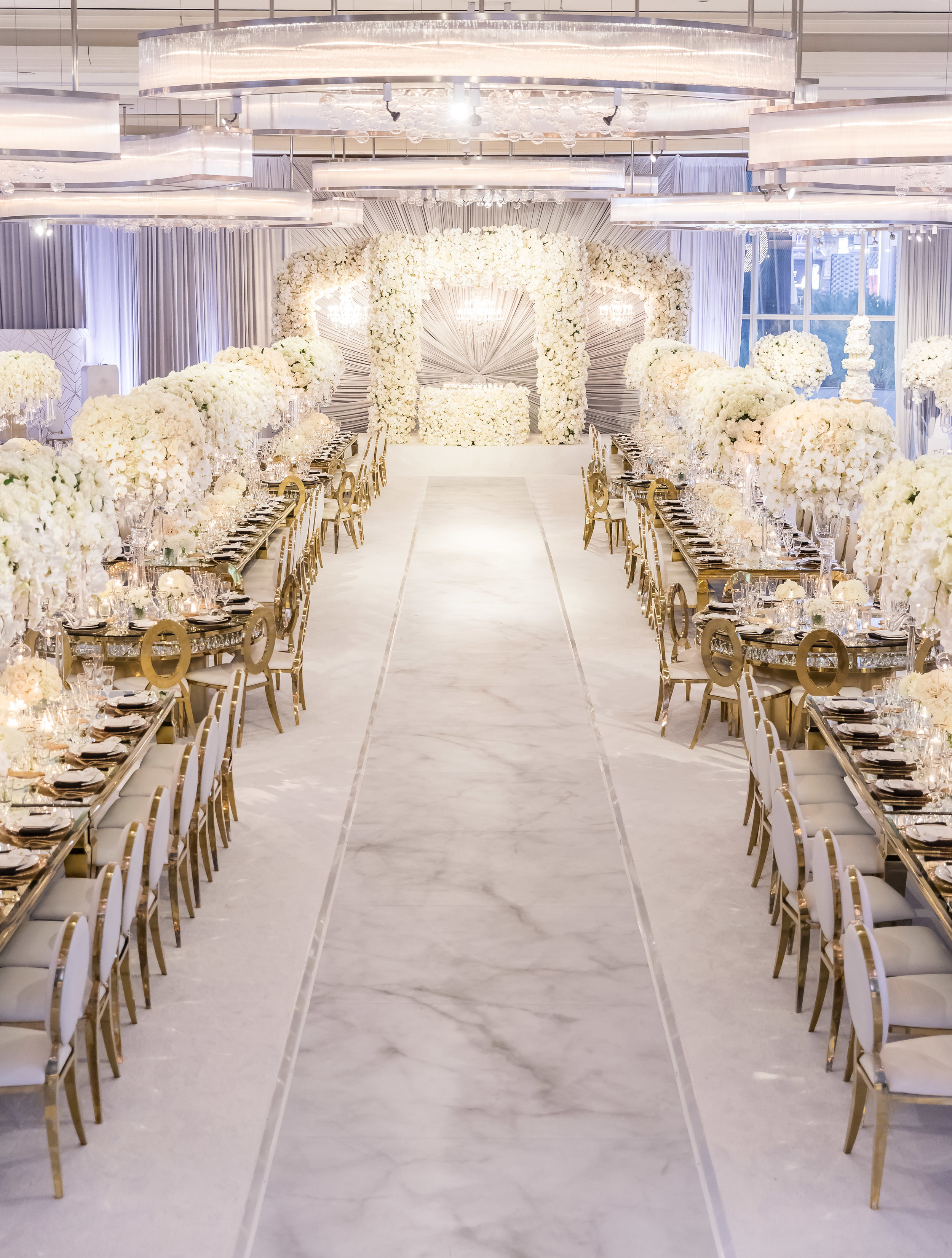 White and marble luxury wedding in Las Vegas with a long center aisle connecting each side.  Designed and Produced by Las Vegas Wedding Planner Andrea Eppolito. Images by Brian Leahy.