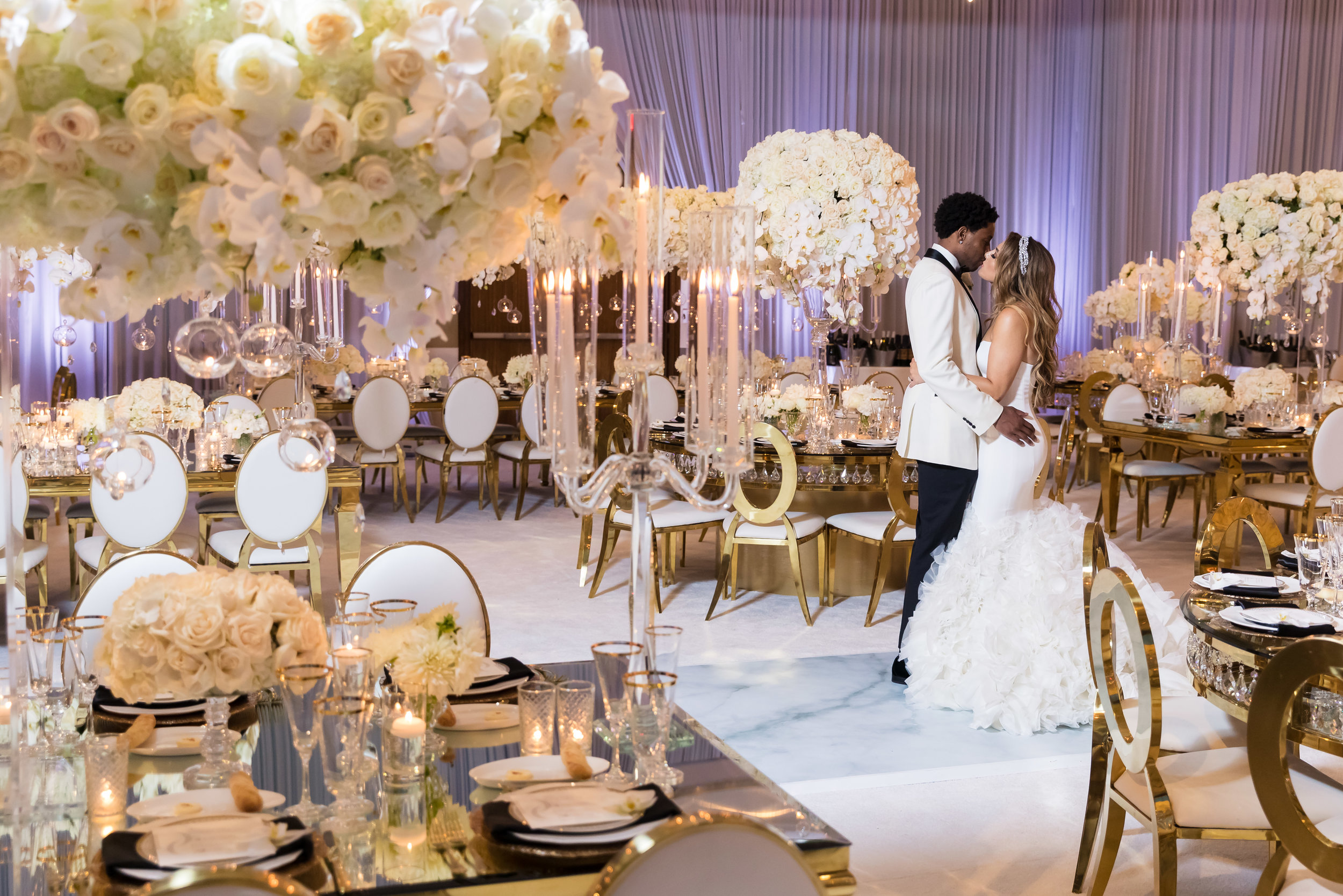 Bride and groom in the middle of their luxe white wedding reception.  Designed and Produced by Las Vegas Wedding Planner Andrea Eppolito. Images by Brian Leahy.