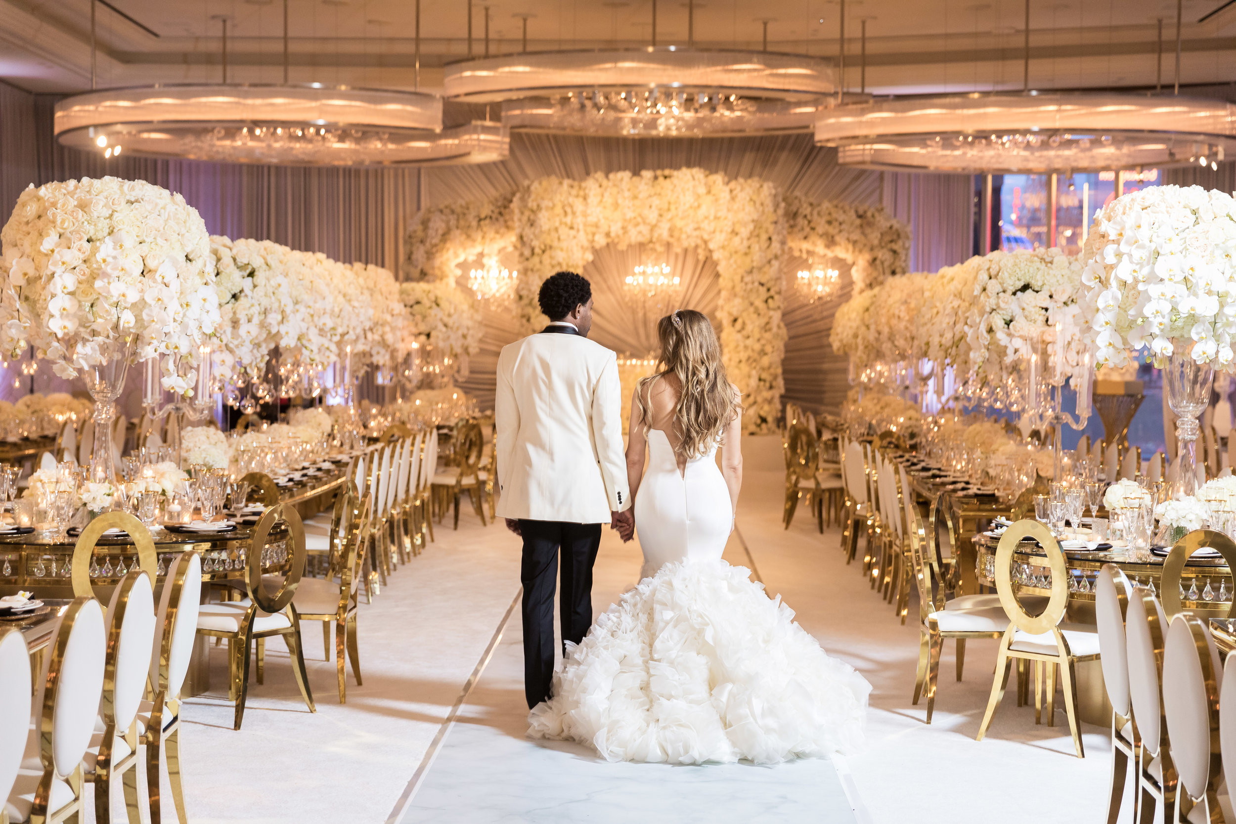 Bride and groom from behind in their wedding reception. Couple on the runway at their wedding.  Designed and Produced by Las Vegas Wedding Planner Andrea Eppolito. Images by Brian Leahy.