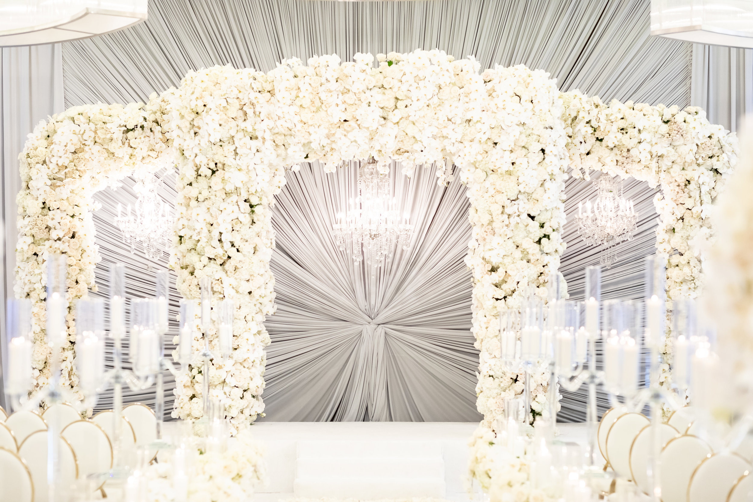 Grey starburst drape behind ceremony flower arch.  Designed and Produced by Las Vegas Wedding Planner Andrea Eppolito. Images by Brian Leahy.