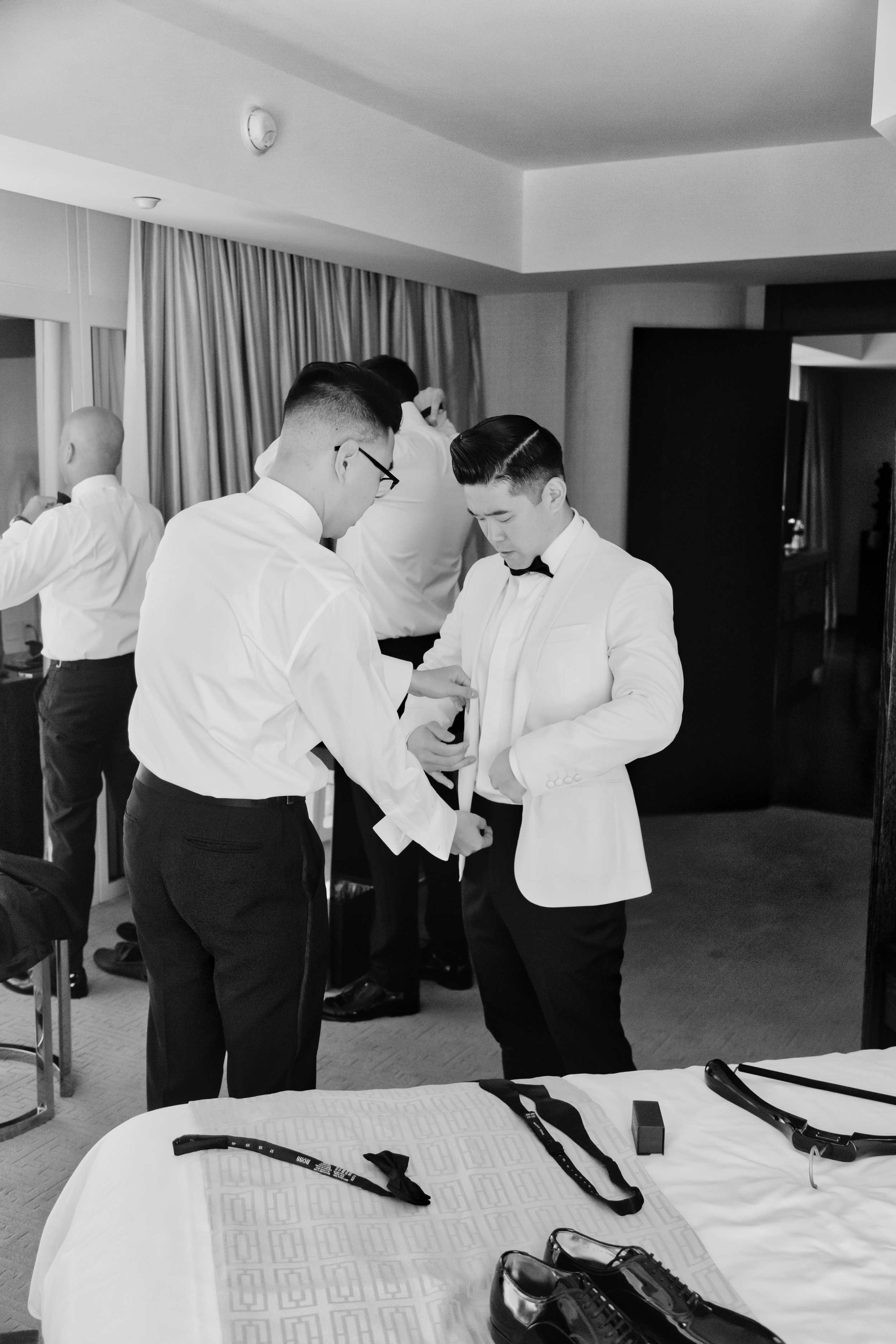 Black and white image of groom getting ready