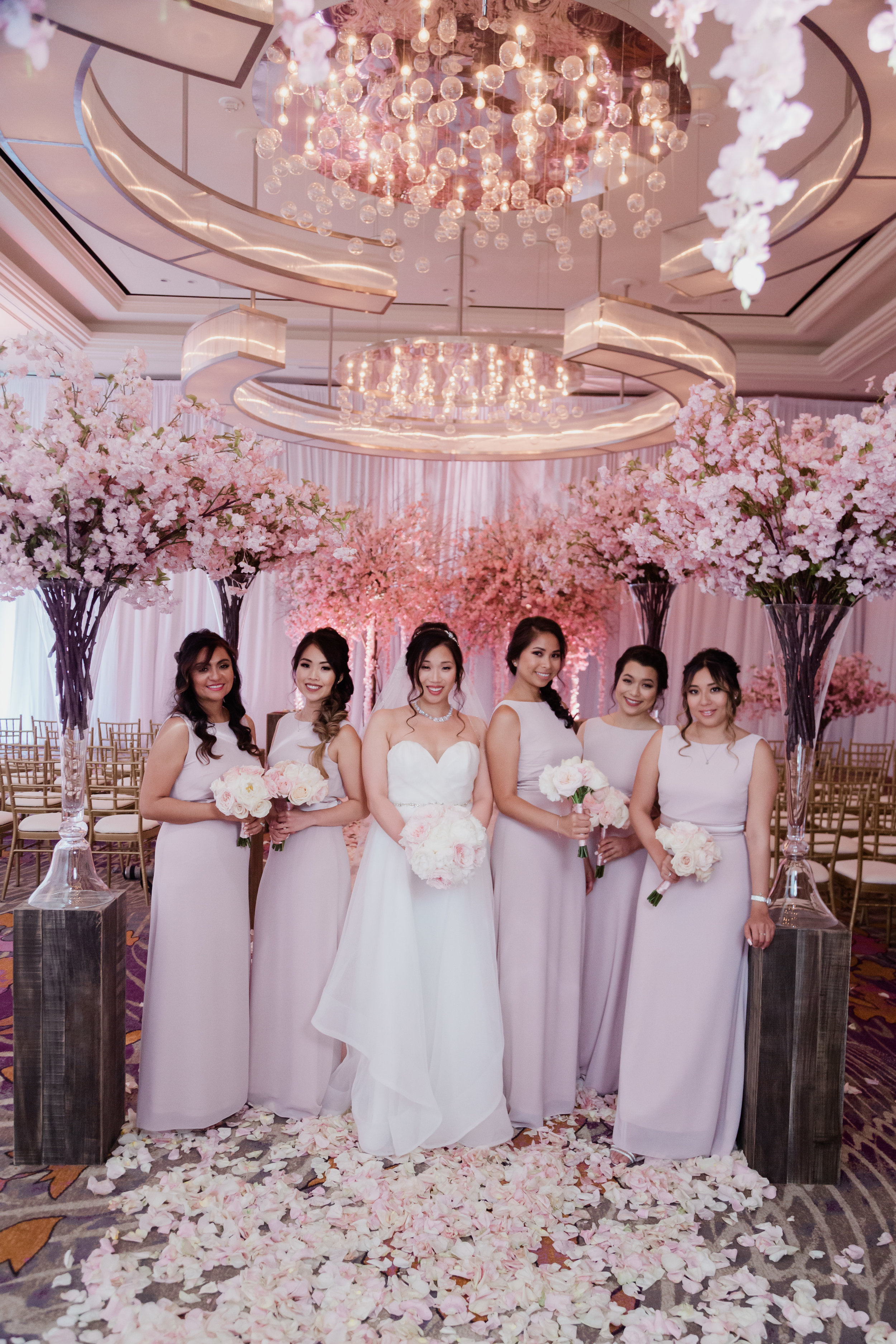 Bridesmaids in pink wedding ceremony with cherry blossom trees. Las Vegas Wedding Planner Andrea Eppolito. Photo by Adam Frazier.