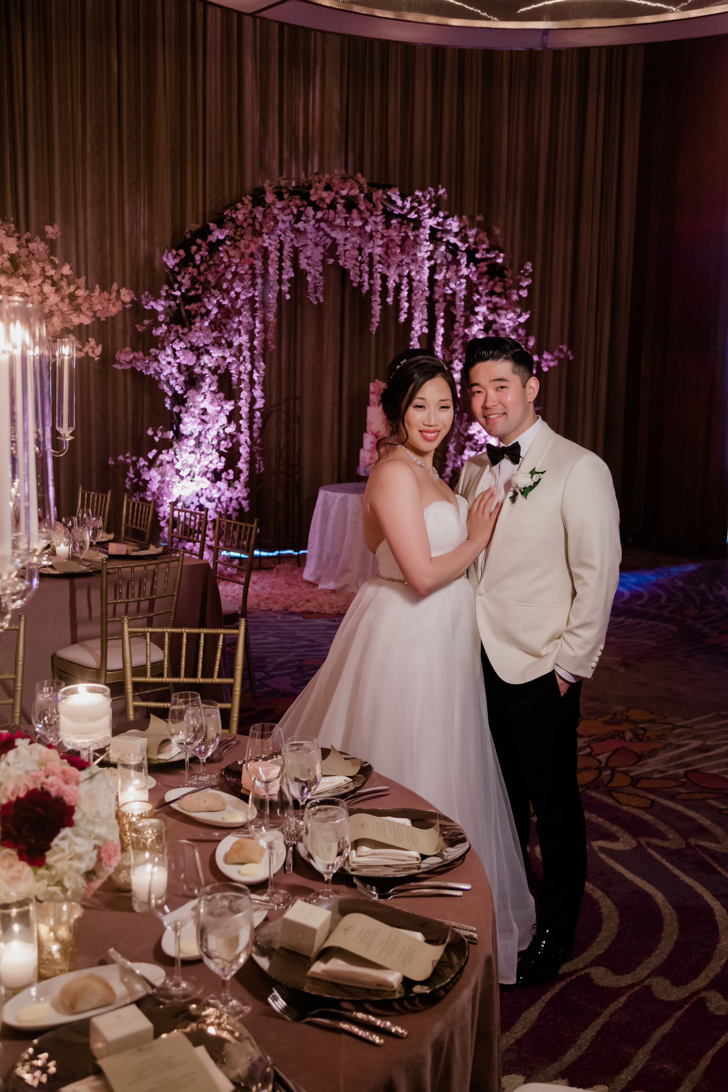 Bride and groom in a pink wedding reception with cherry blossom arch. Las Vegas Wedding Planner Andrea Eppolito. Photo by Adam Frazier.
