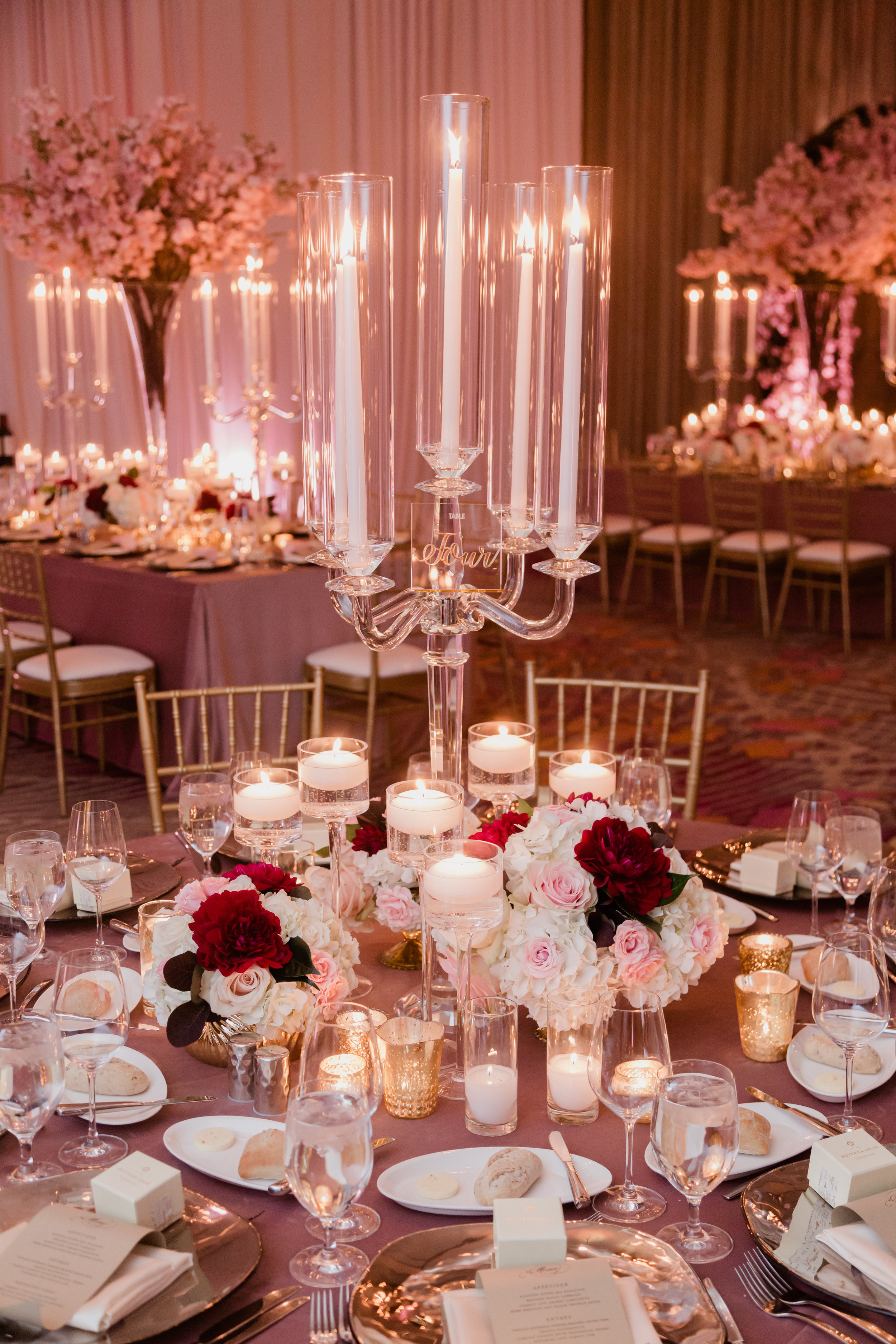 Candelabras and flowers on the center of a round tables in Las Vegas. Las Vegas Wedding Planner Andrea Eppolito. Photo by Adam Frazier.