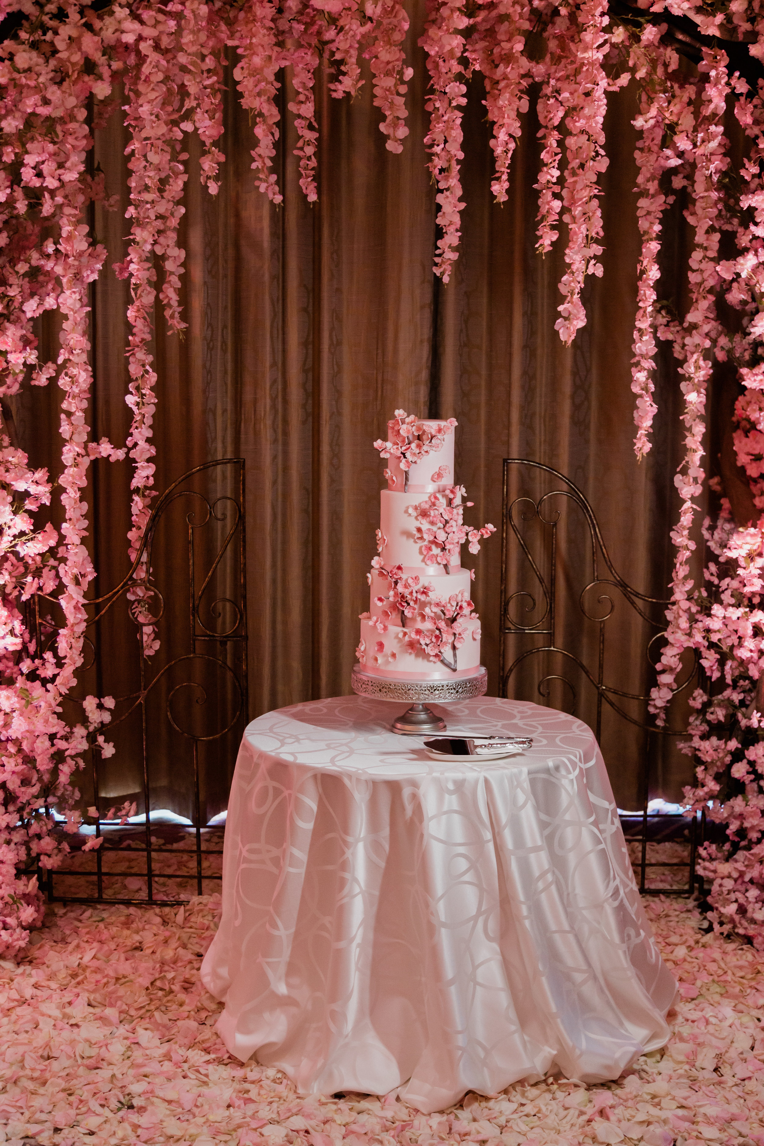 Cherry blossom wedding cake surrounded by pink flowers. Las Vegas Wedding Planner Andrea Eppolito. Photo by Adam Frazier.