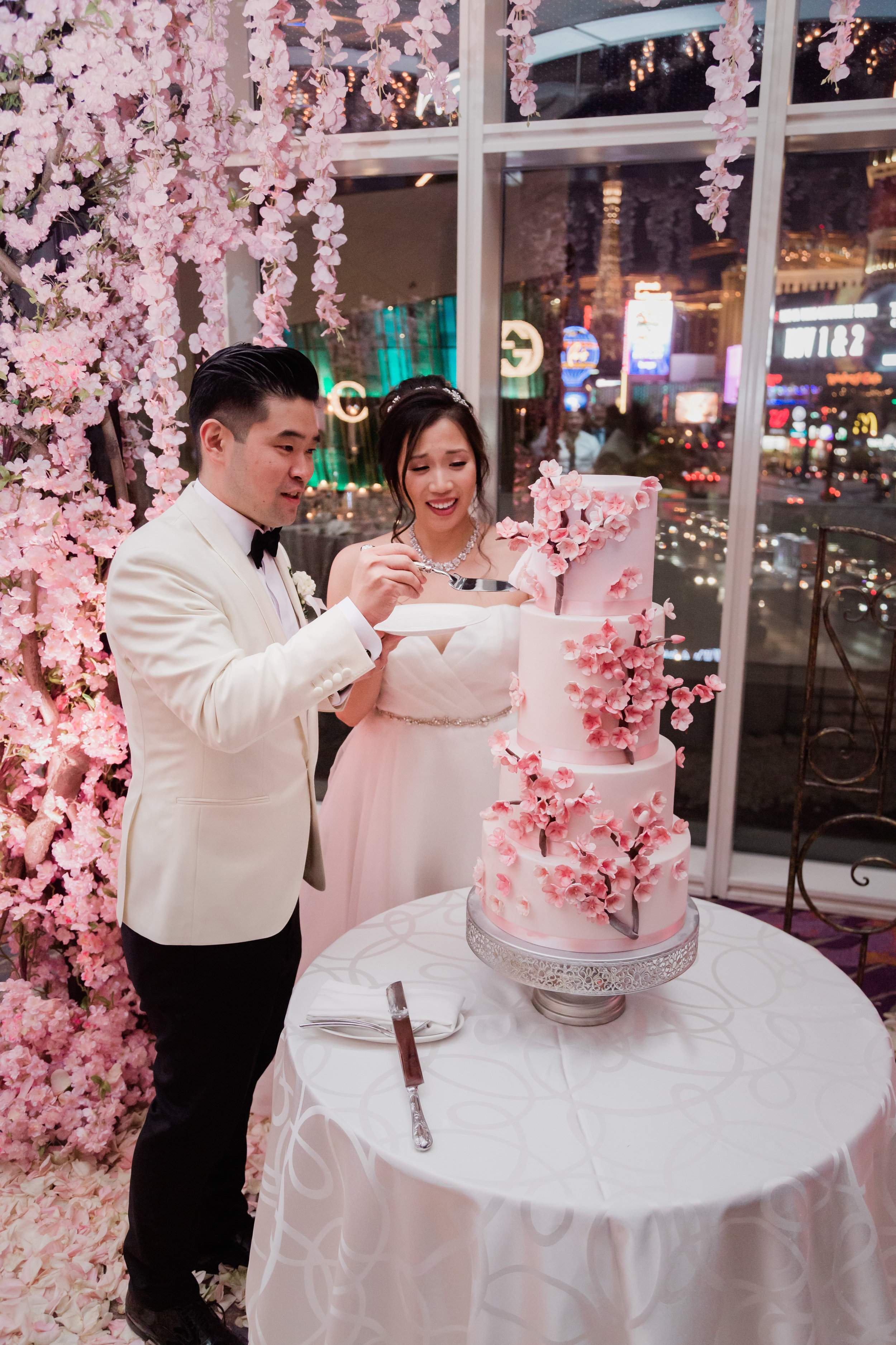 Bride and groom cutting a wedding cake with cherry blossoms on it. Las Vegas Wedding Planner Andrea Eppolito. Photo by Adam Frazier.