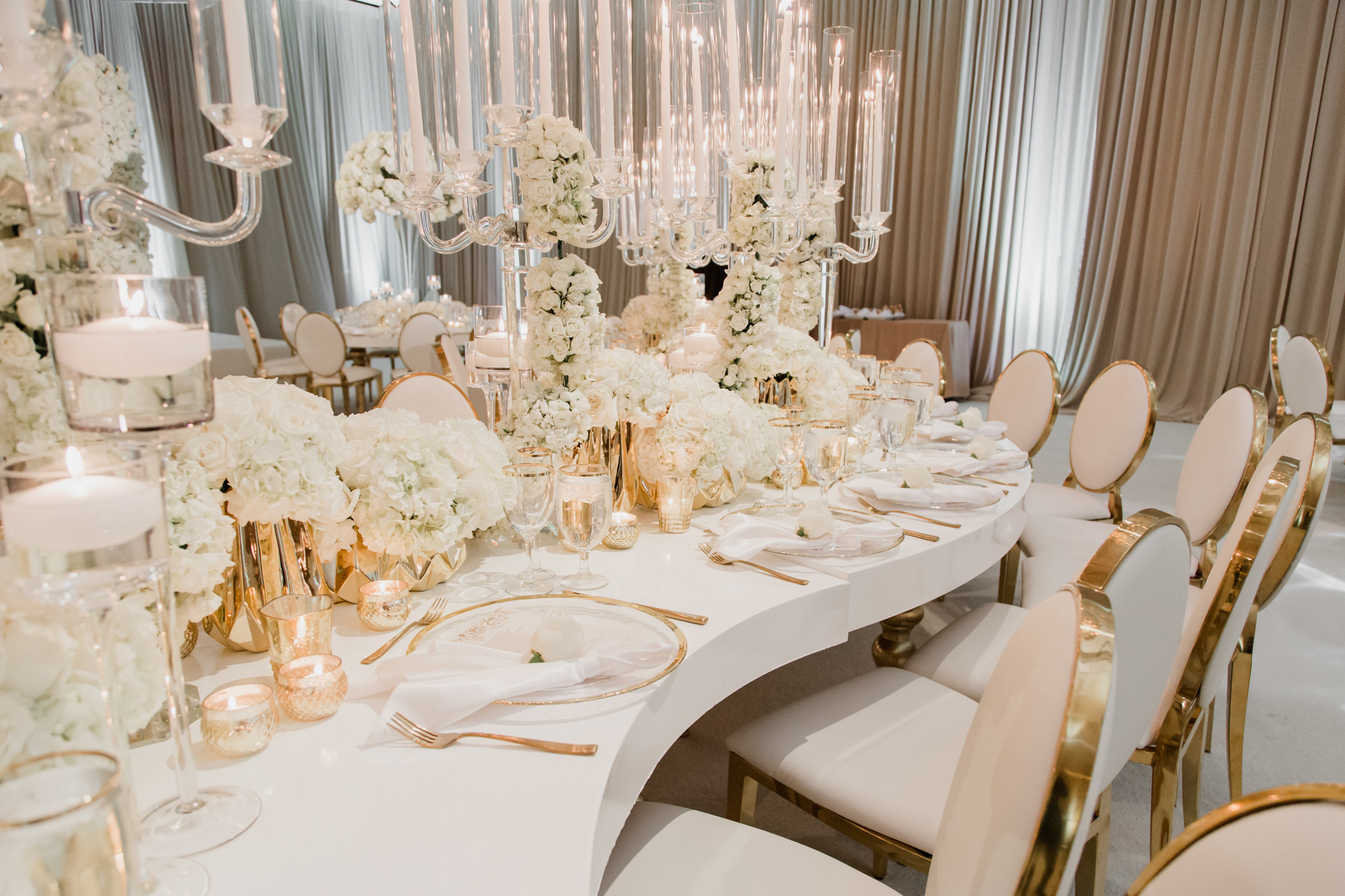 DESIGN TIP:  Curved serpentine tables fees fresh and whimsical, while the stark white makes the shape a stand out in the room.  The circular gold rimmed chargers anchor the table and give it a sense of tradition.  Las Vegas Wedding Planner Andrea Eppolito. Image by Adam Frazier.