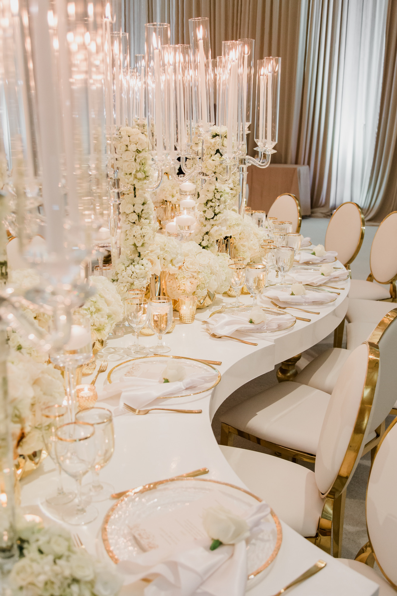 Long white serpentine wedding tables with gold rimmed chargers.  Las Vegas Wedding Planner Andrea Eppolito. www.andreaeppolitoevents.com. Image by Adam Frazier.