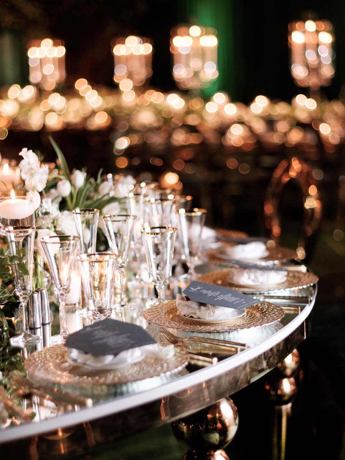 Mirror topped tables with black menus and gold chargers at ARIA Las Vegas Wedding. Luxury Las Vegas Wedding Planner Andrea Eppolito. www.andreaeppolitoevents.com. Photo by Rene Zadori.