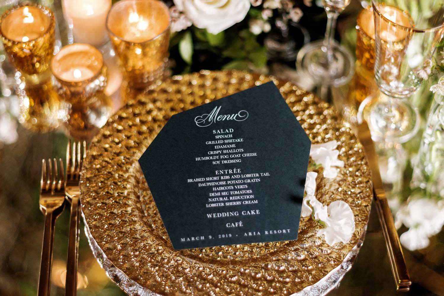 Black hexagon menu by Meldeen on gold charger at luxury Las Vegas Wedding at ARIA. Luxury Las Vegas Wedding Planner Andrea Eppolito. www.andreaeppolitoevents.com. Photo by Rene Zadori.