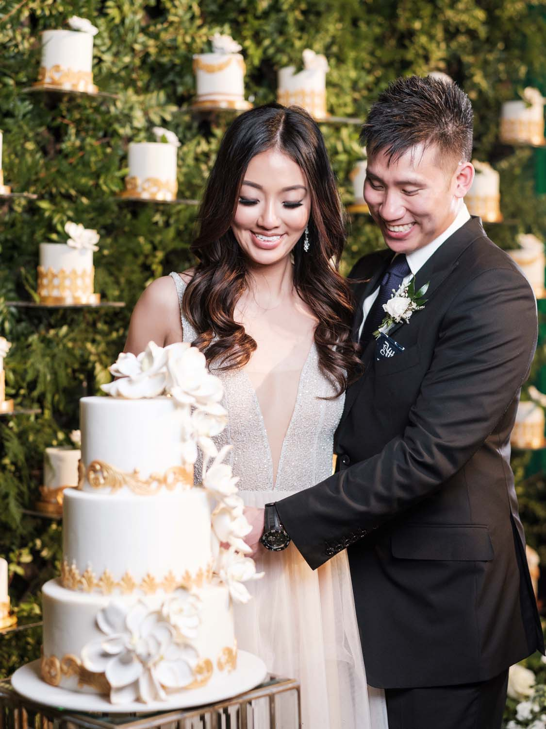 The bride and groom cut the cake surrounded by individual mini wedding cakes. Luxury Las Vegas Wedding Planner Andrea Eppolito. www.andreaeppolitoevents.com. Photo by Rene Zadori.
