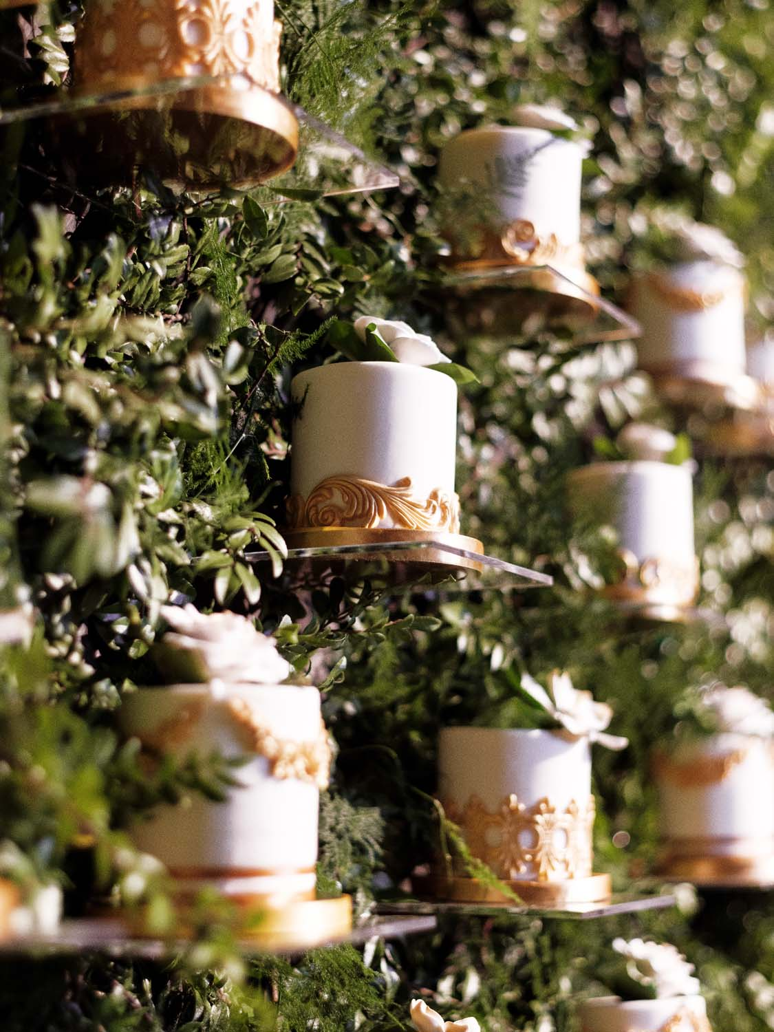 Hedge wall of floating individual wedding cakes. Luxury Las Vegas Wedding Planner Andrea Eppolito. www.andreaeppolitoevents.com. Photo by Rene Zadori.