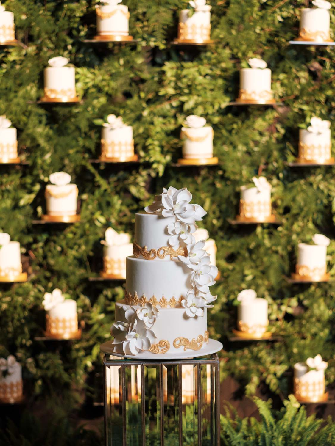 White and gold wedding cake in front of a wall of mini individual wedding cakes at luxury wedding at ARIA Las Vegas. Luxury Las Vegas Wedding Planner Andrea Eppolito. www.andreaeppolitoevents.com. Photo by Rene Zadori.