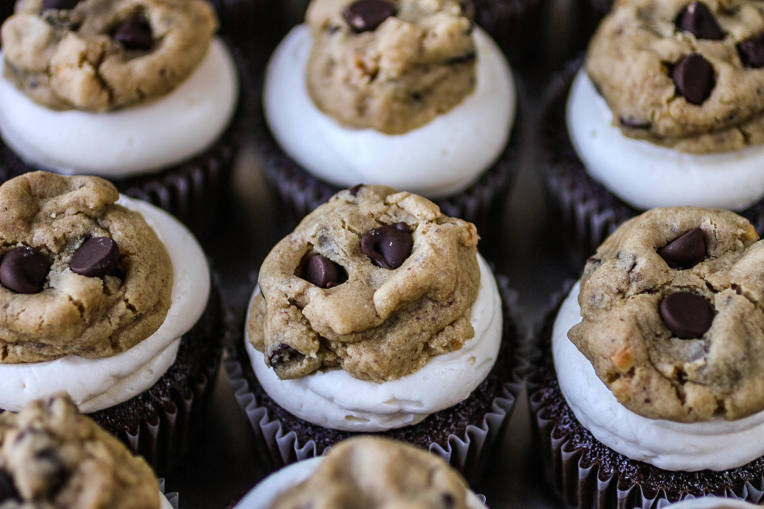 cookie dough filled cupcake topped with chocolate chip cookie