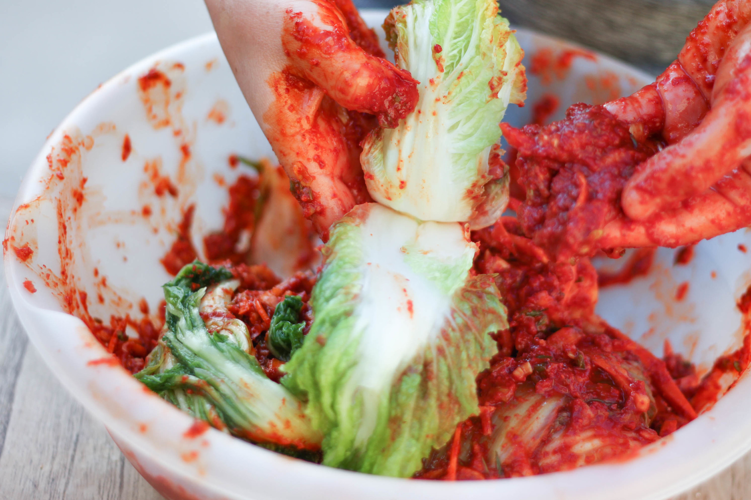 Spread kimchi paste thoroughly onto napa cabbage. Don't be lazy. Make sure to get in-between the leaves.