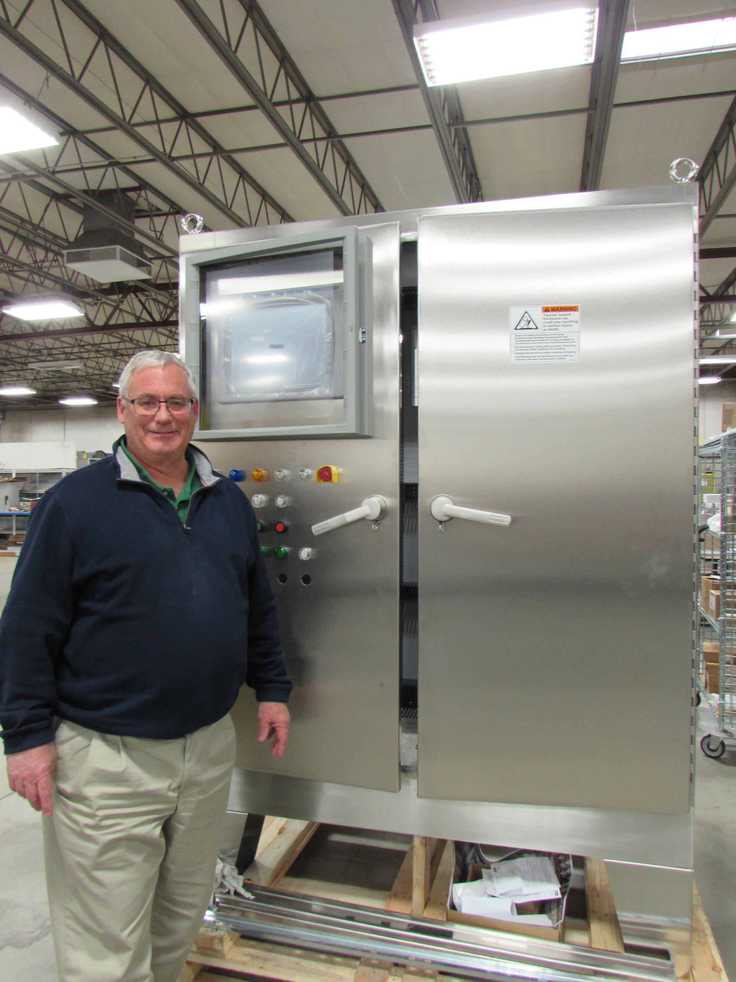 John Quinn standing next to a Hoffman stainless steel enclosure.