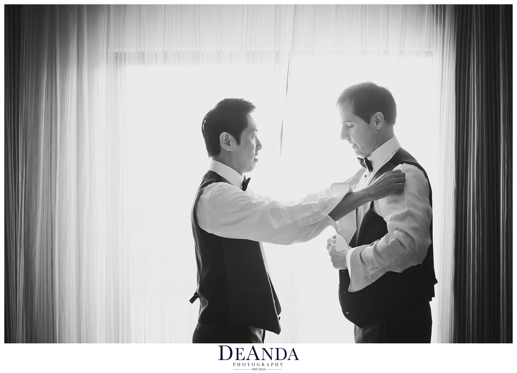 grooms helping each other get ready together in black and white in chicago