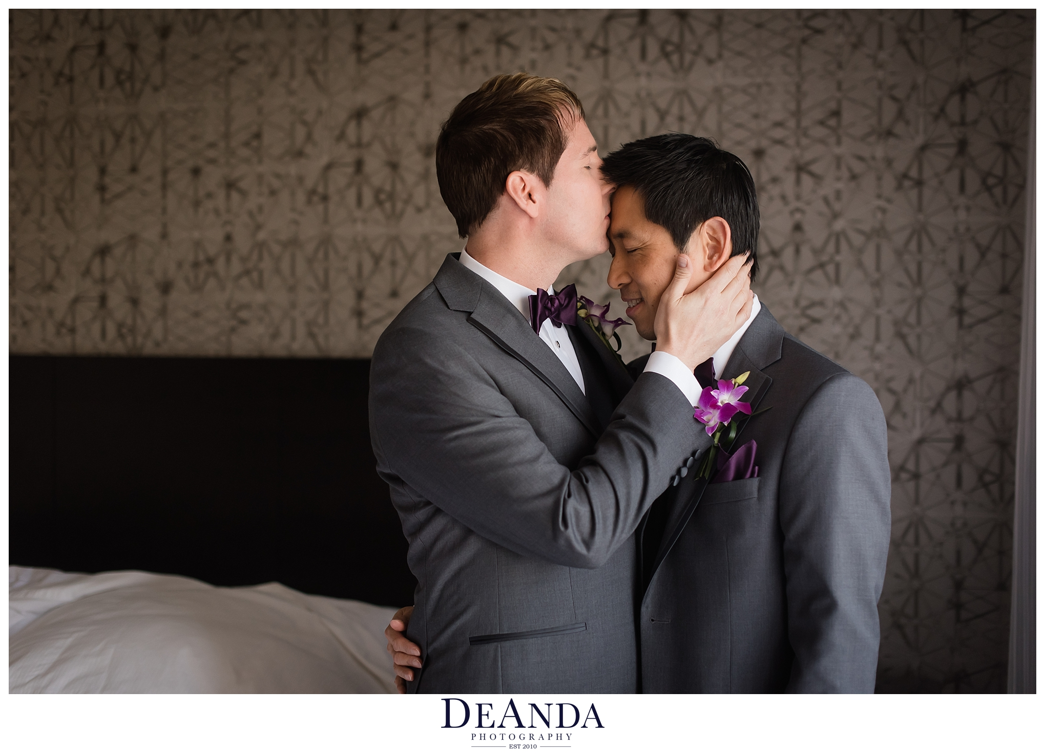 two grooms kissing in hotel room