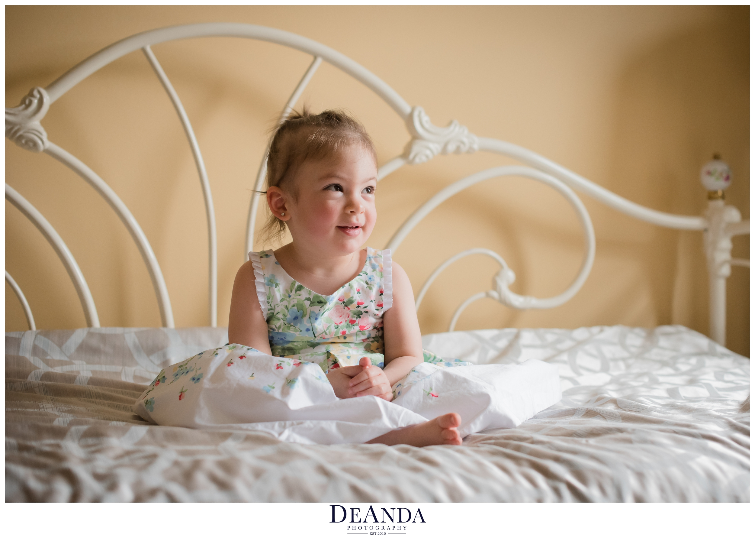 little girl sitting on bed for 2 year old portraits