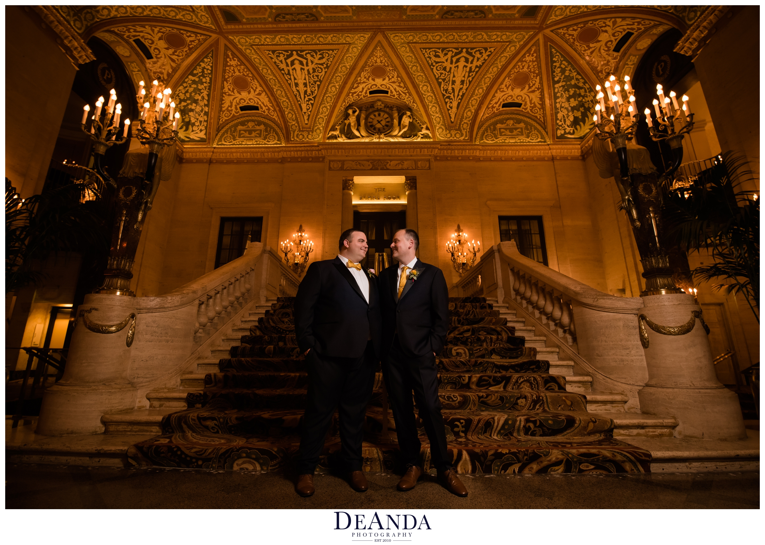 grooms together at palmer house hotel on stairs