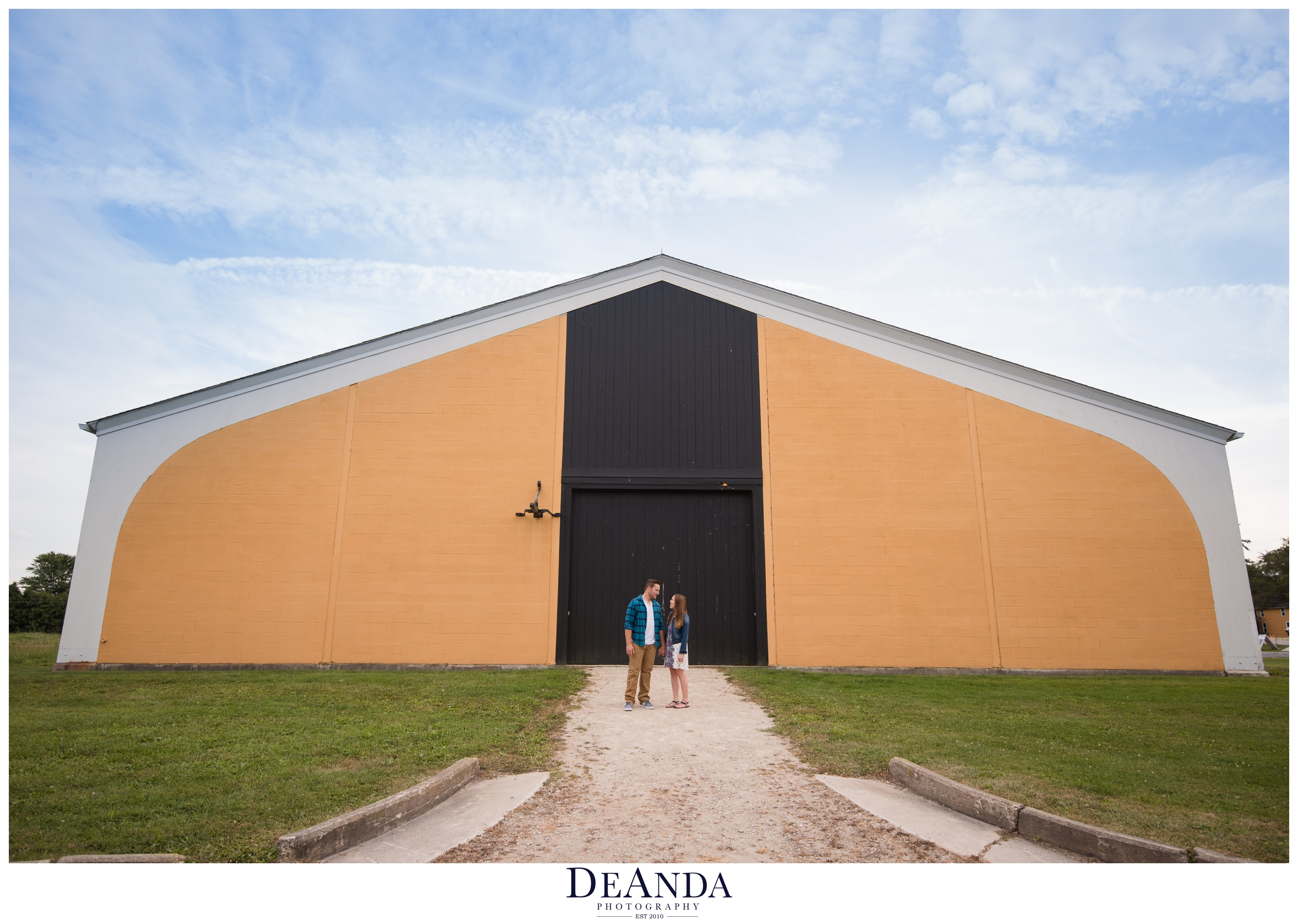 st.james farm engagement photos in front of indoor arena