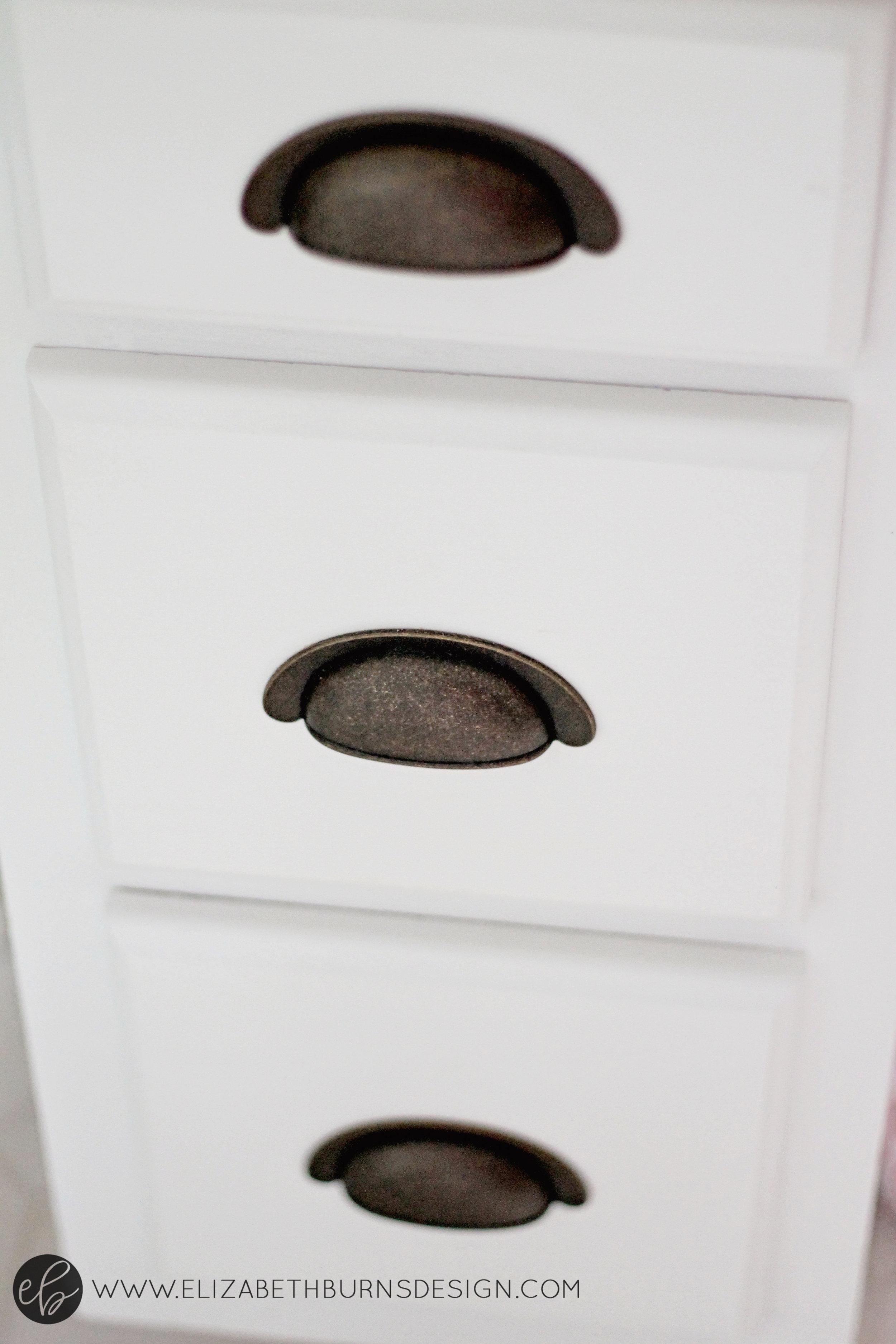 Elizabeth Burns Design | Raleigh Interior Designer -old oak cabinets painted white in builder grade kitchen with dark hardware; hardware to match brass hinges on kitchen cabinets