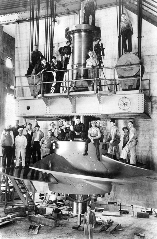 Historic photograph of an original turbine from the WPA-builtBonneville Dam withthe men who made it (andwhose presence also very cleverly provides all-important scale). Image courtesy Bonneville Dam Authority.