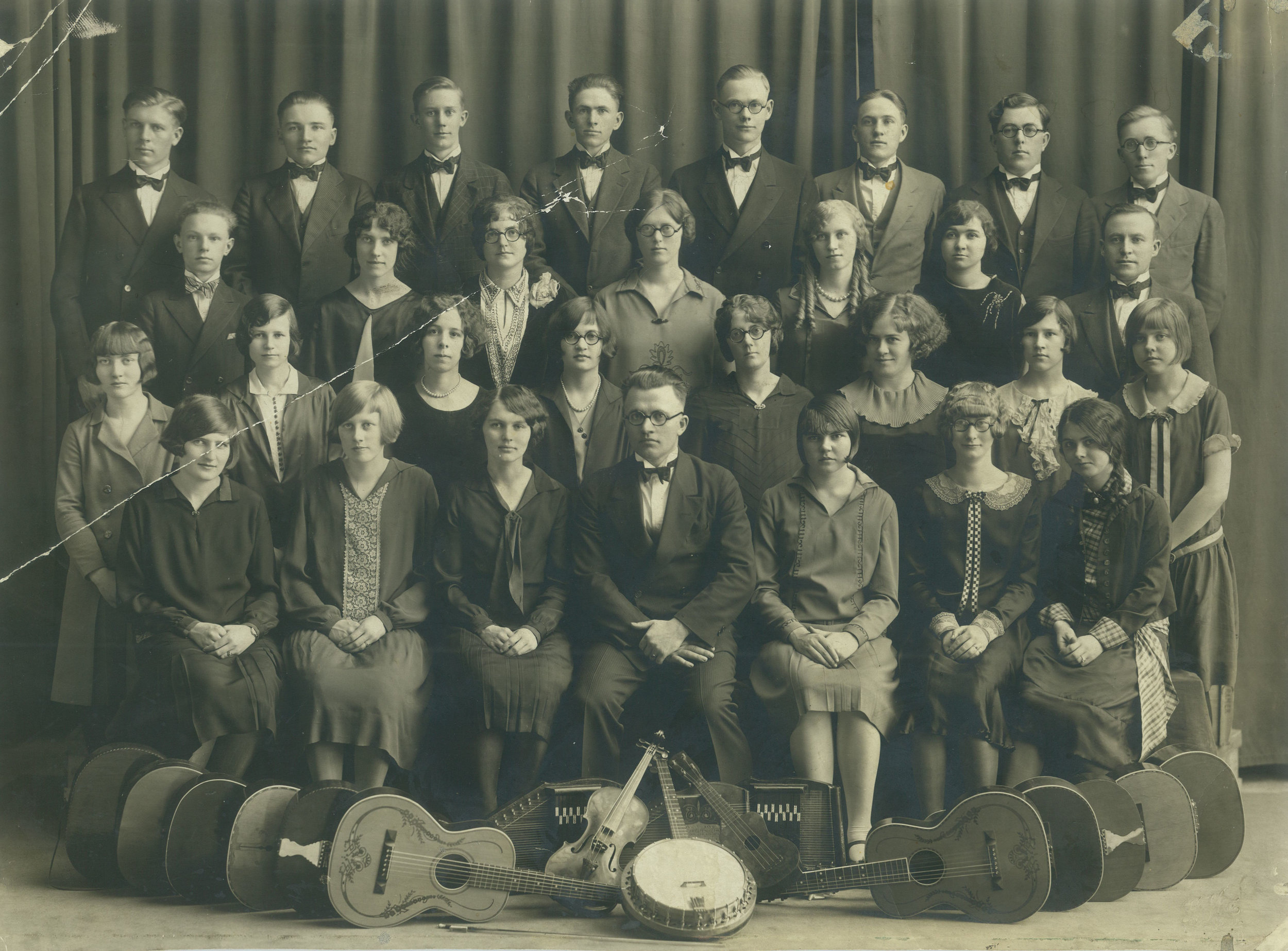 The 1925-26 string band was a highlight for Minnie, standing third from the right in the second row. Her proficiency on the harp opened doors for her to tour with the group throughout Minnesota and North Dakota.