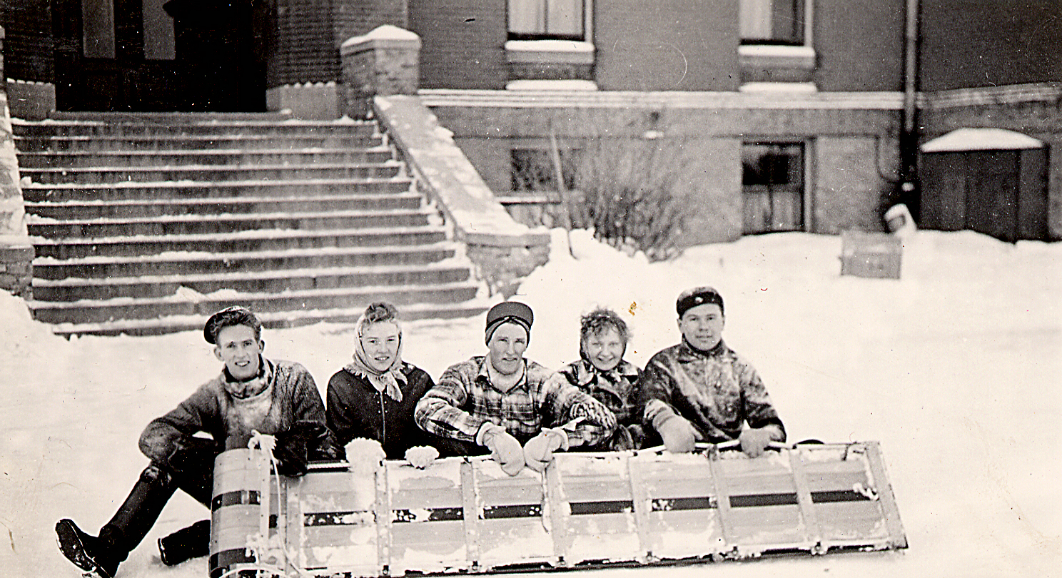 Students pose by the front steps of Hillcrest before jogging to the back of the Castle to toboggan on Hillcrest's campus in the 1940s.