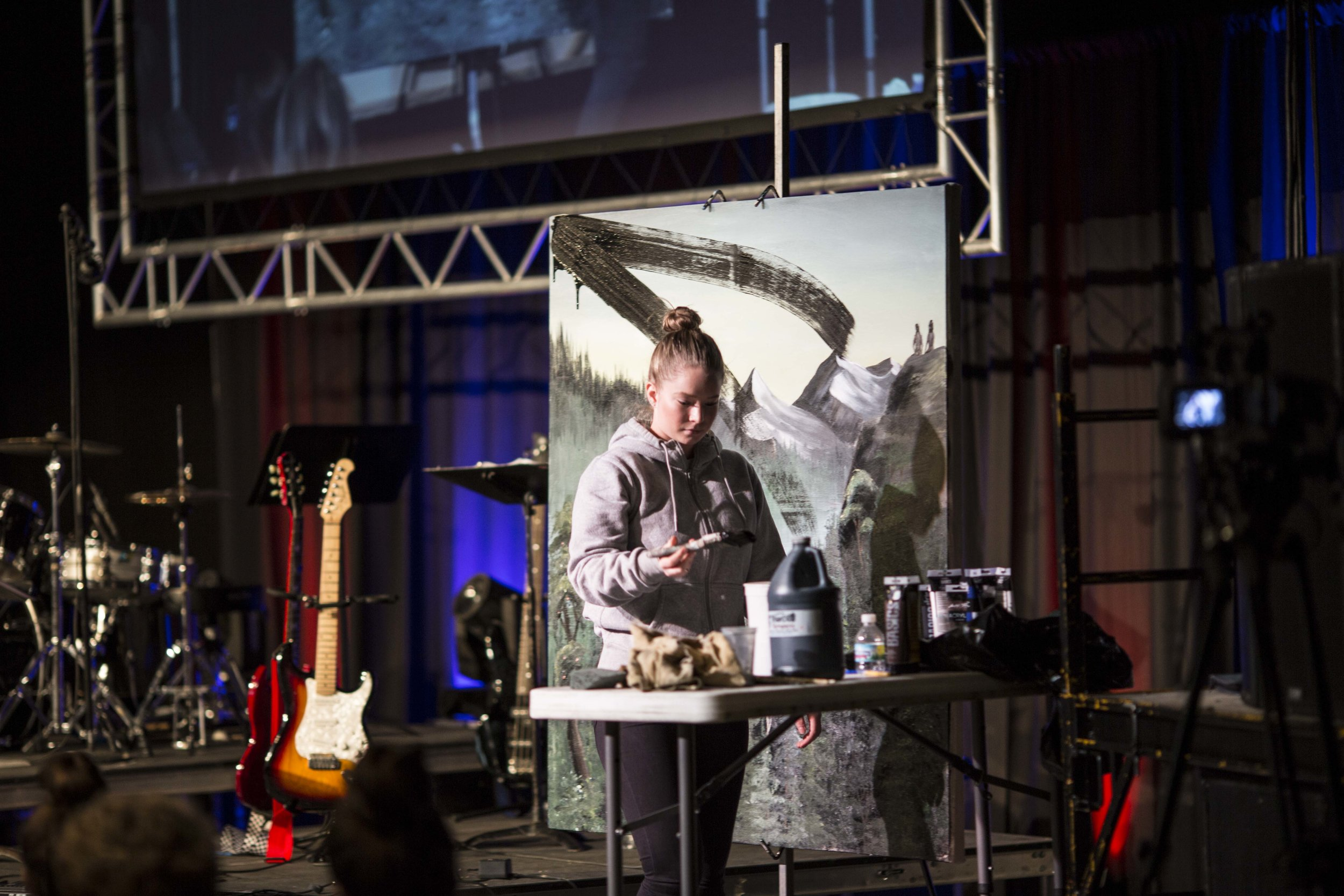 Leonora Tuvin paints over Sylvia's painting, an artistic depiction of the fall, during day two of Prayer Day