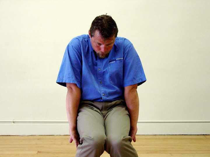 On an exhale slowly flex your body, coming into a slouched position where everything is shortened in the front. Start small and then allow it to get larger. Get to this full shortened position in increments, move from your centre, rolling your pelvis back and letting the rest of your body move with it.