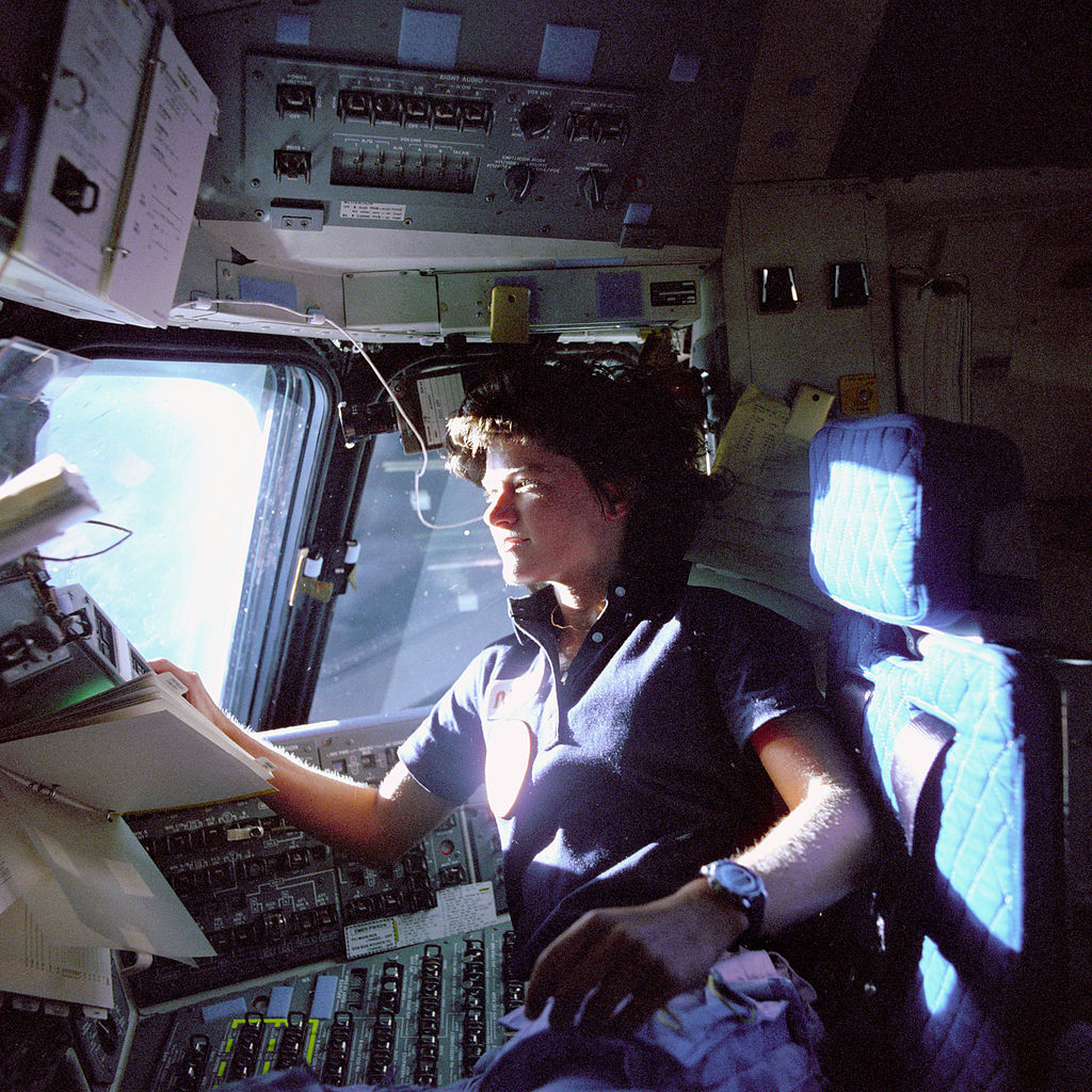 Astronaut Sally K. Ride, mission specialist on STS-7, monitors control panels from the pilot's chair on the Flight Deck. Floating in front of her is a flight procedures notebook, NASA (Great Images in NASA Description) [public domain],  via Wikimedia Commons