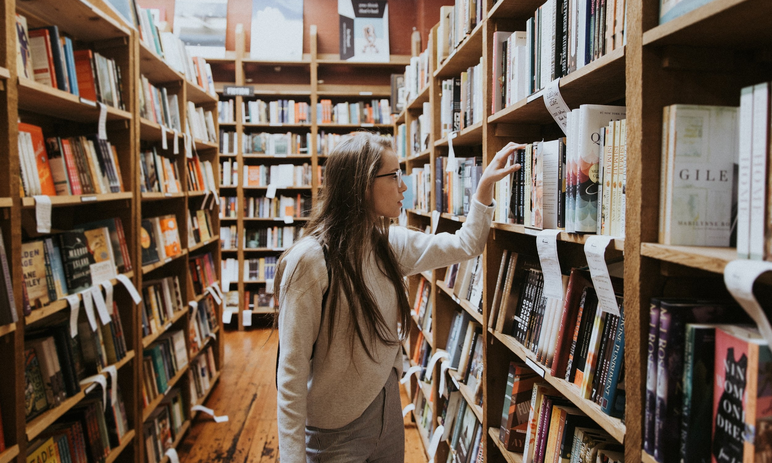 young woman browsing through library shelves
