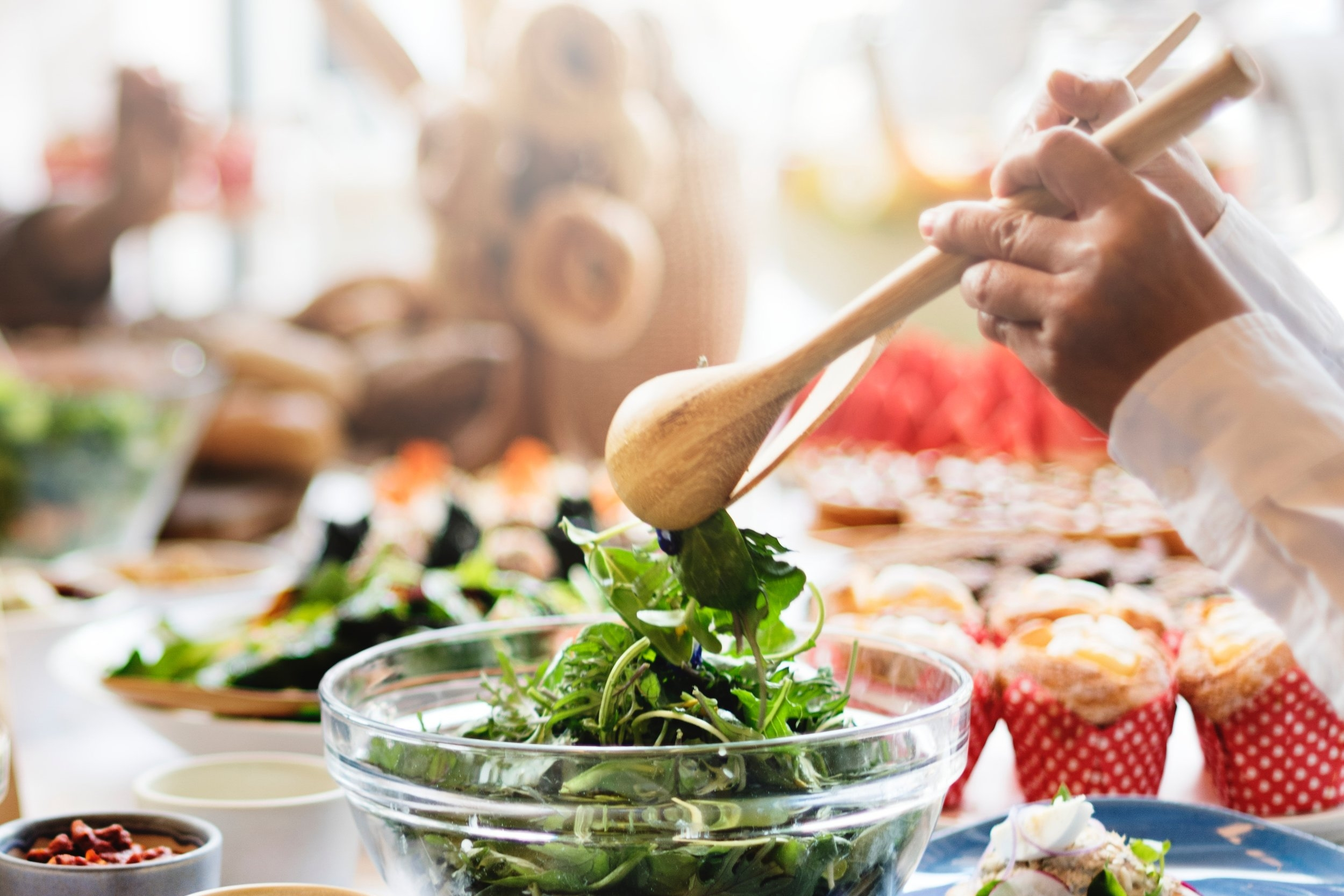 a chef tosses a salad with wooden spoons on a table filled with breakfast foods