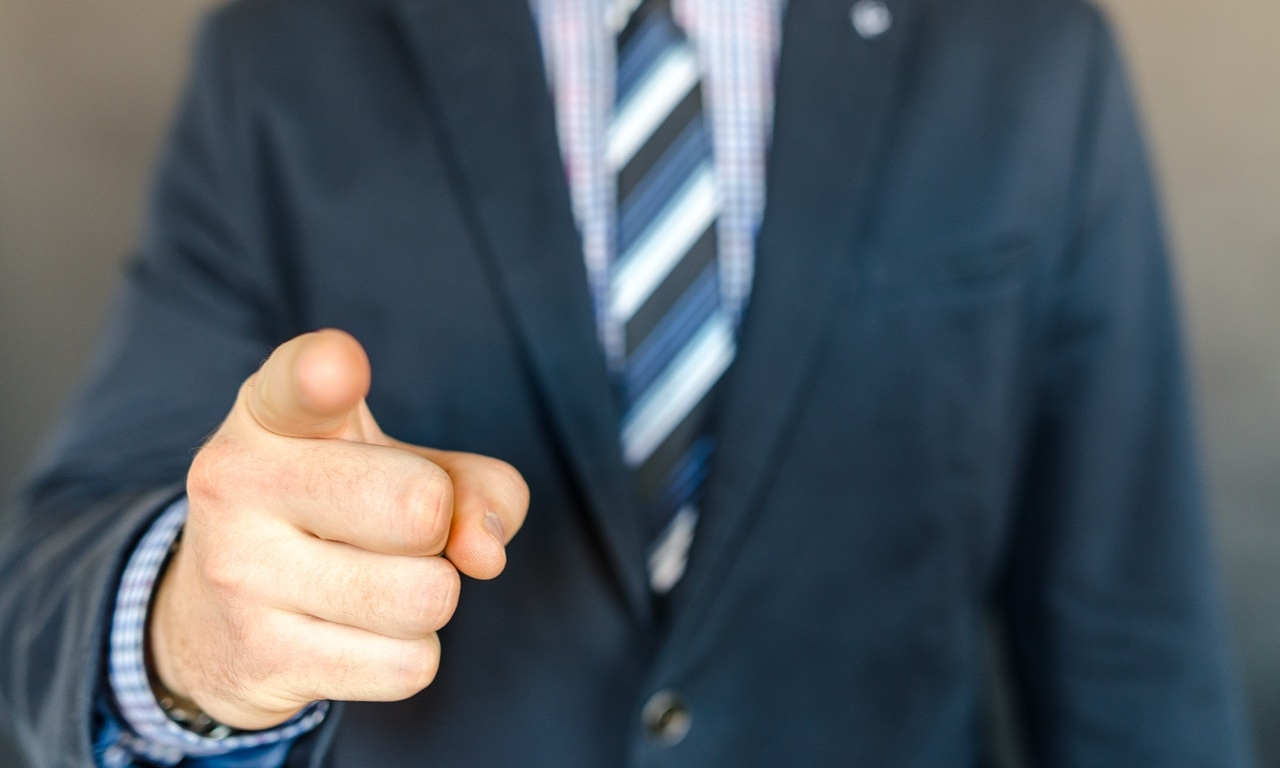 a closeup of a man in a suit's pointing finger