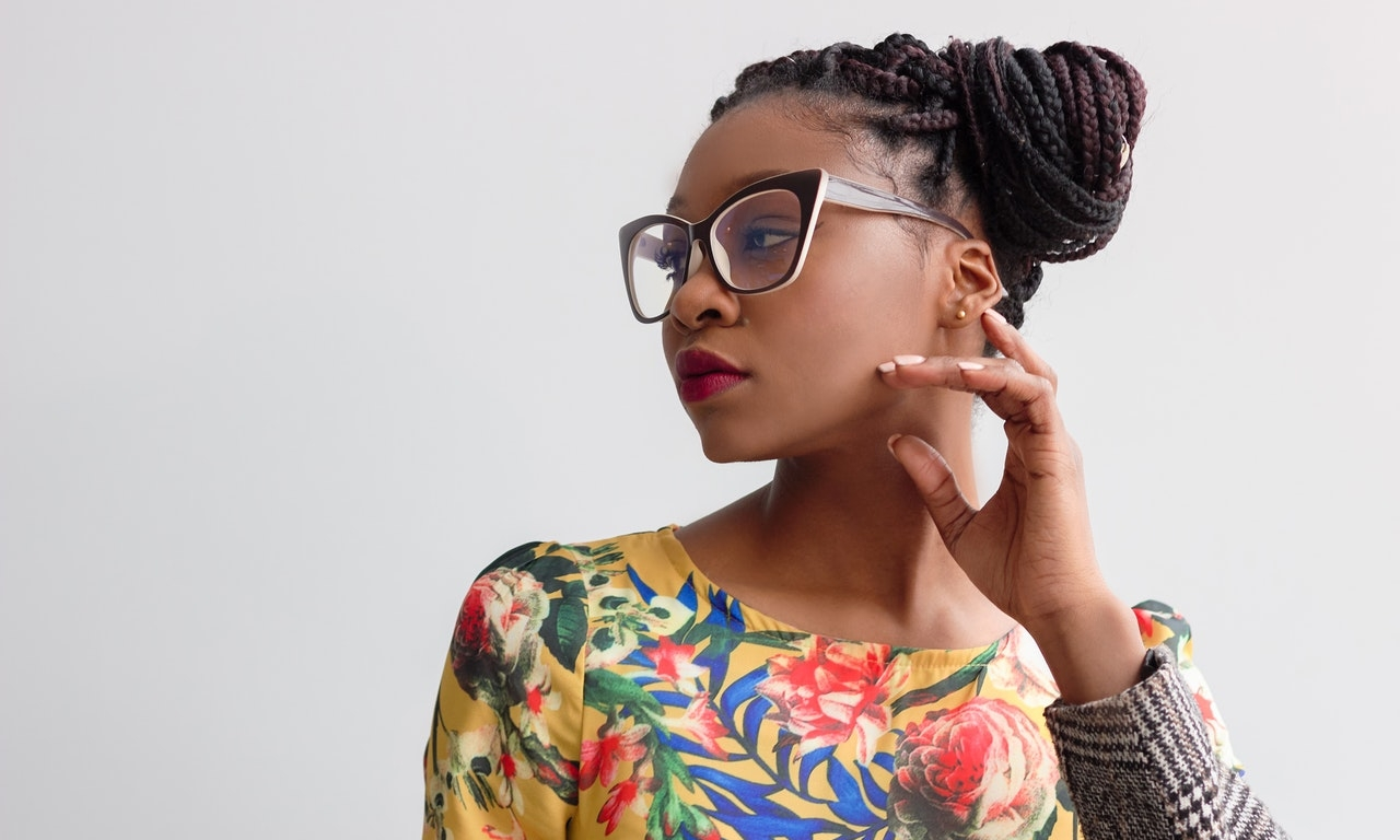 a Black woman professional wearing glasses and looking like she's thinking