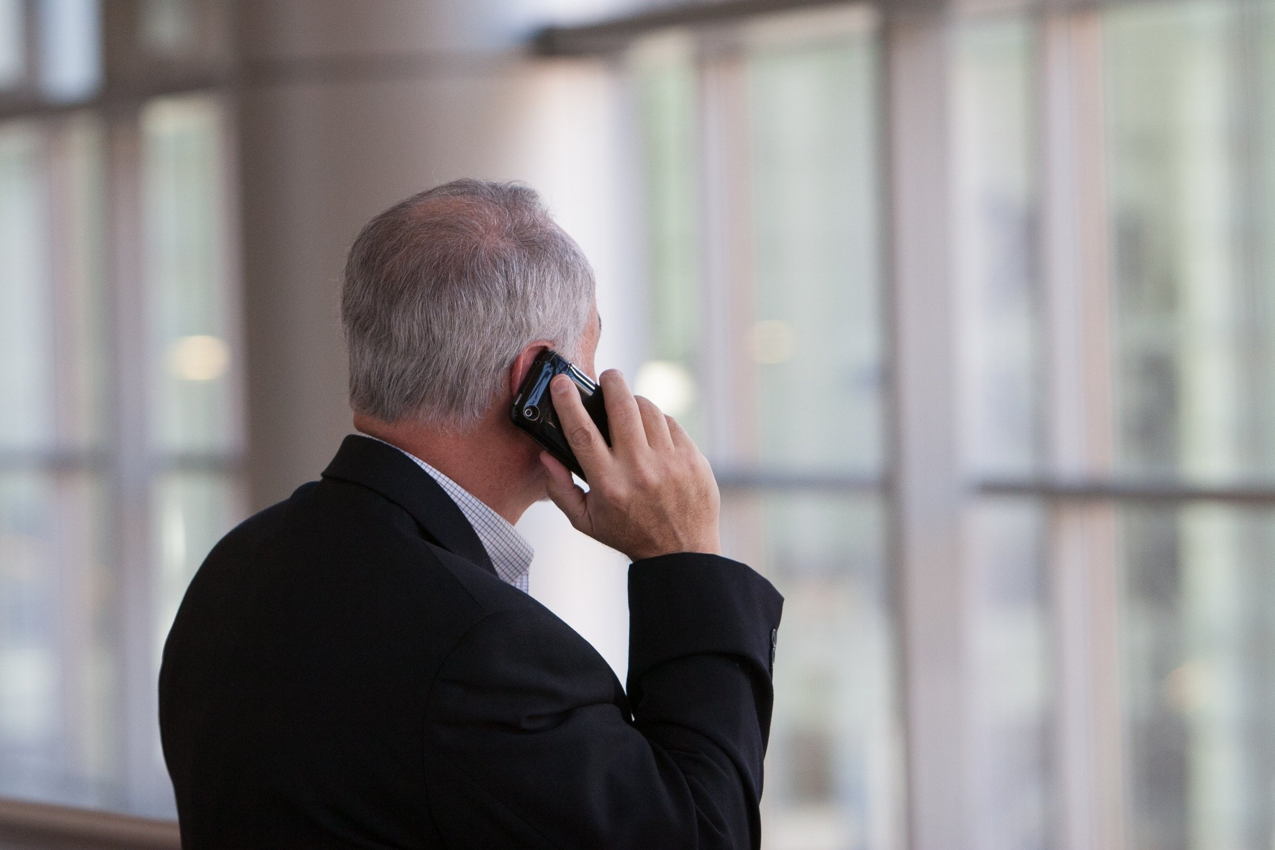 a silver-haired man talking on the phone looking out a window