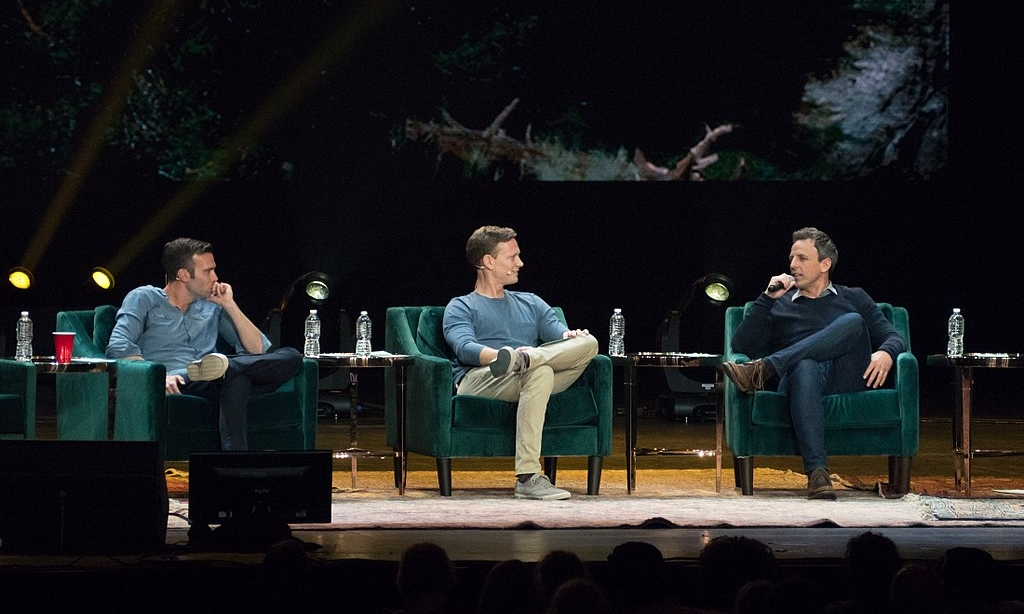 Jon Favreau, Tommy Vietor, and guest Seth Meyers at a live taping of  Pod Save America  at Radio City Music Hall in New York City in May 2018. Photo credit: Rhododendrites [ CC BY-SA 4.0 ],  via Wikimedia Commons  (cropped)