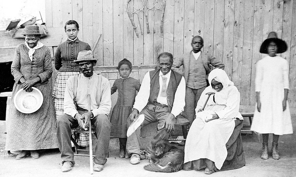 "Harriet Tubman with family and neighbors at her home in Auburn, NY in 1887. Left to right: Harriet Tubman, Gertie Davis, Nelson Davis, Lee Chaney, ""Pop"" John Alexander, Walter Green, and Blind ""Aunty"" Sarah Parker, Dora Stewart. Photo credit: William H. Cheney [public domain],  via Wikimedia Commons  (cropped)"