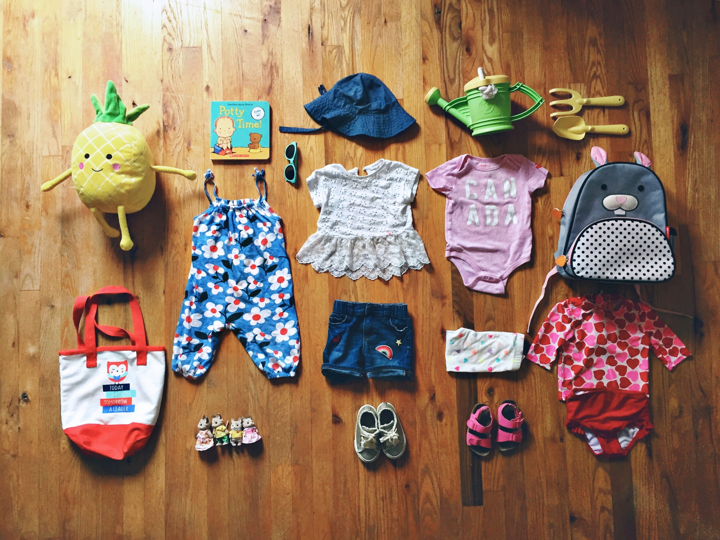 From top centre - clockwise:  Hat     Carters  , watering can & tools     Indigo,   Bunny Skip Hop Backpack     Indigo,   Heart swimsuit     Joe Fresh,   Canada Outfit     Joe Fresh,   Heart Pants     Children's Place,   Sandles     Joe Fresh  , Lace Shoes    Zara,  Jean Shorts     The Gap,   Lace Top    Korea,  Green Sunglasses     Carters  , Blue & White Flower Romper    Joe Fresh,  4 Calico Critters     The Bay,   Canvus bag     Chapters/Indigo,   Pineapple Guy   Gift from  Auntie Nicole,  Potty Time Book     Indigo.