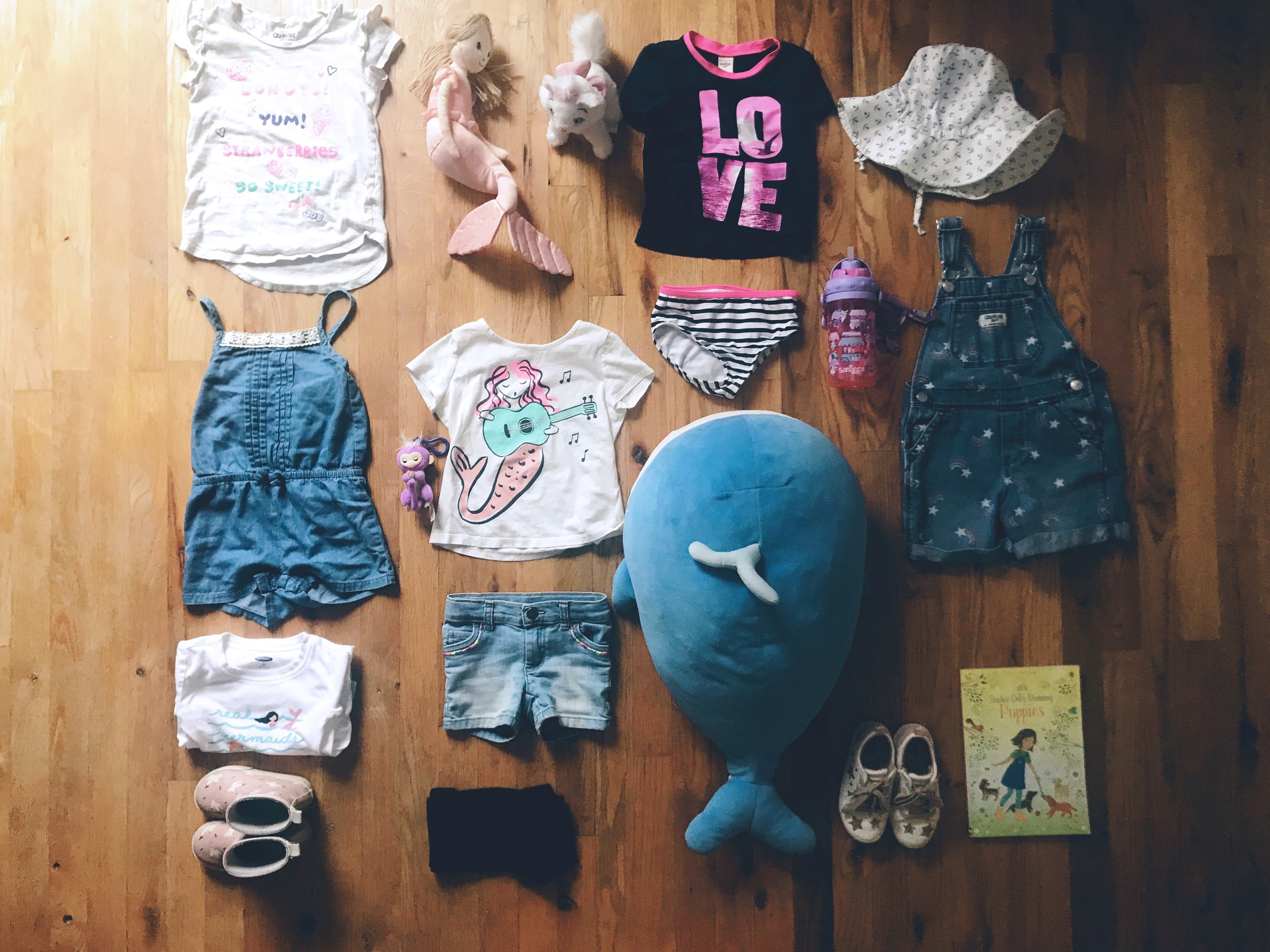 Top centre - Clockwise :  White Cat Marie - Aristacat  | Gift from Auntie Heidi,  LOVE Swimsuit   | Joe Fresh,   Anchor Hat   | Fluffy Bottom Babies,   Rainbow Overalls   | Carters,   Water Bottle  | Gift from Yeye from trip to Hong Kong,  Puppies Sticker Book   | From Indigo for PEI road trip,   Star Sneakers   | Zara,   Whale  | long ago gift from Auntie Nicole,  Black Shorts   | Joe Fresh,   Rain Boots   | H&M,   Mermaid Pyjamas   | Carters,   Jean Shorts   | Carters,   Jean romper   | Carters,   Fingerling key chain  | gift from family friend,  Mermaid t-shirt  | Second hand find from Auntie Nicole,  Donought t-shirt     | Carters,   Mermaid   | Fluffy Bottom Babies