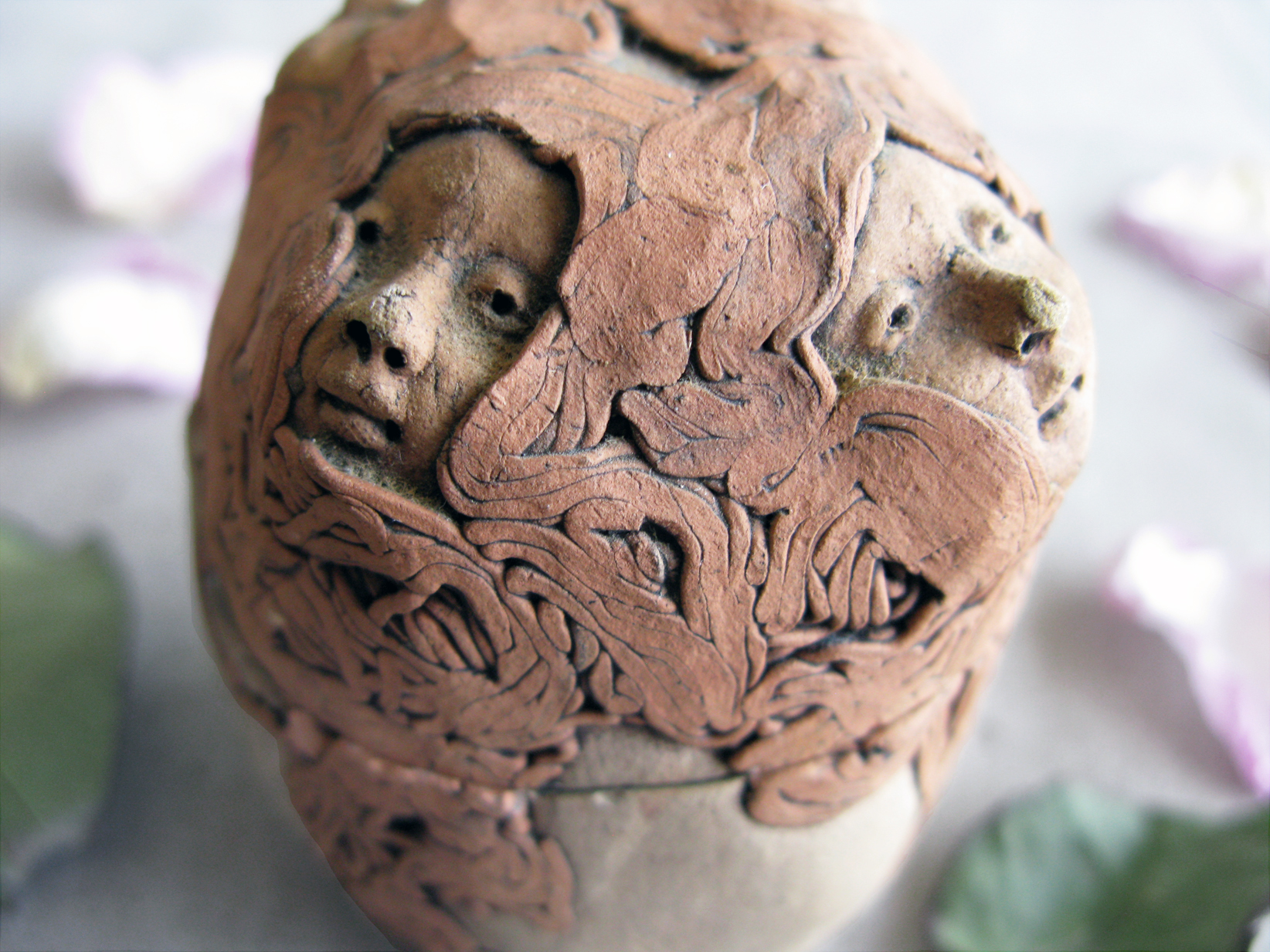 pottery jar with heads