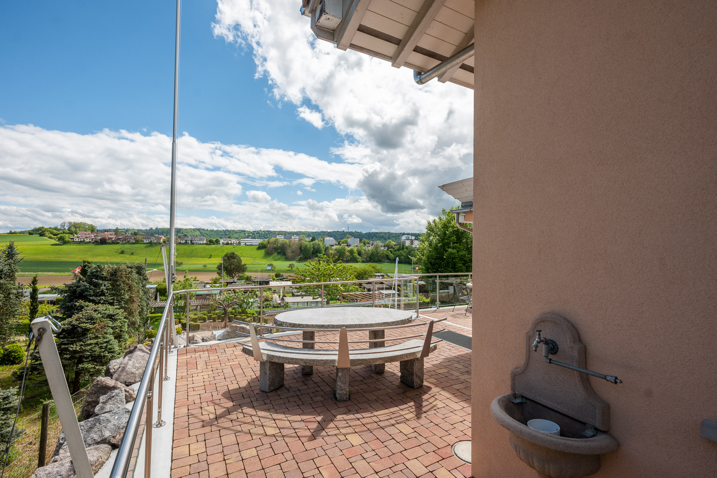 Teil der Terrasse im mittleren Geschoss mit Granitbank und -tisch