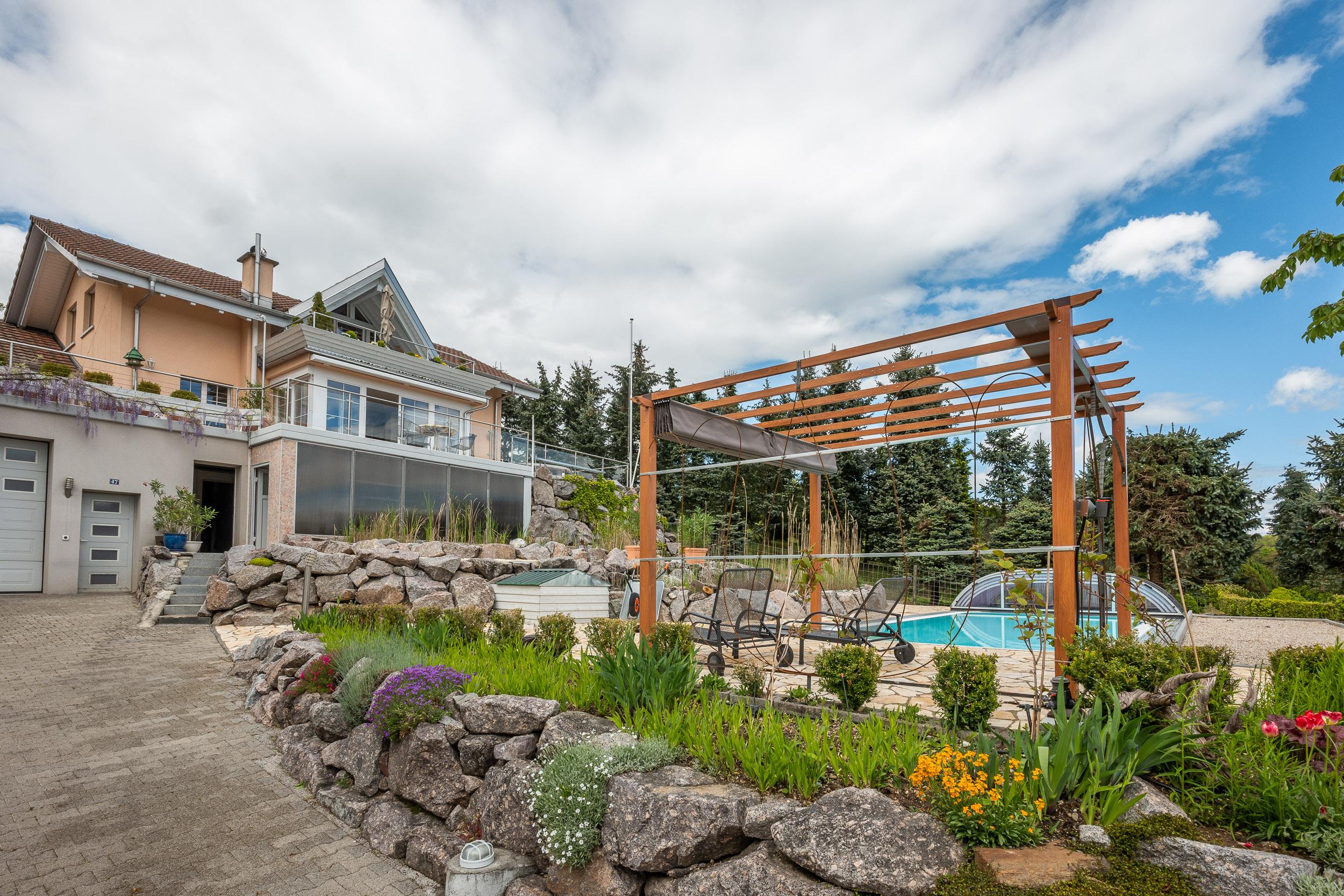 Blick von unten an das Haus und die Gartenanlage mit Swimmingpool und Naturteichen