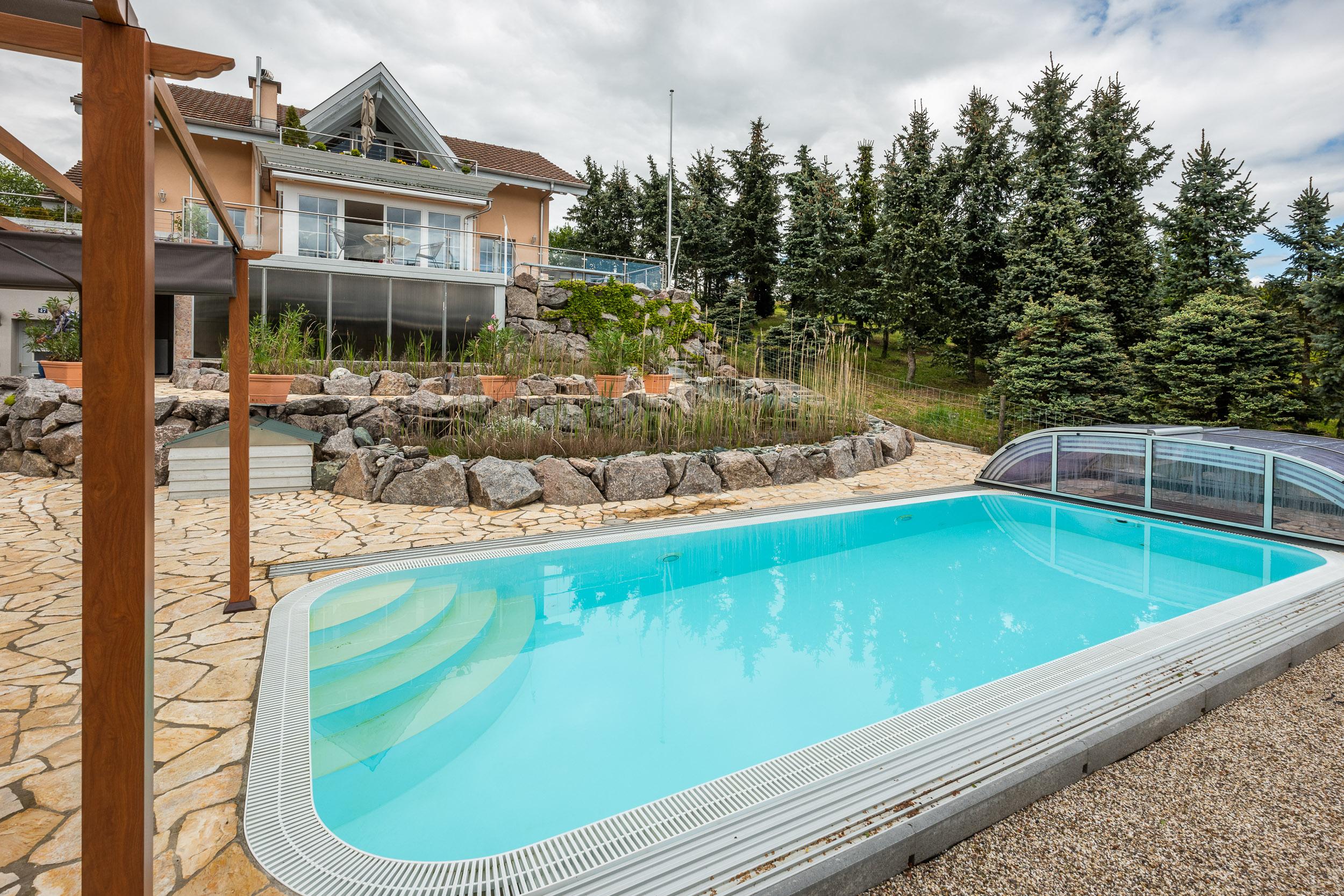 Abdeckbarer Swimmingpool. Im Pool kann man sich auch bei geschlossenem Dach aufhalten