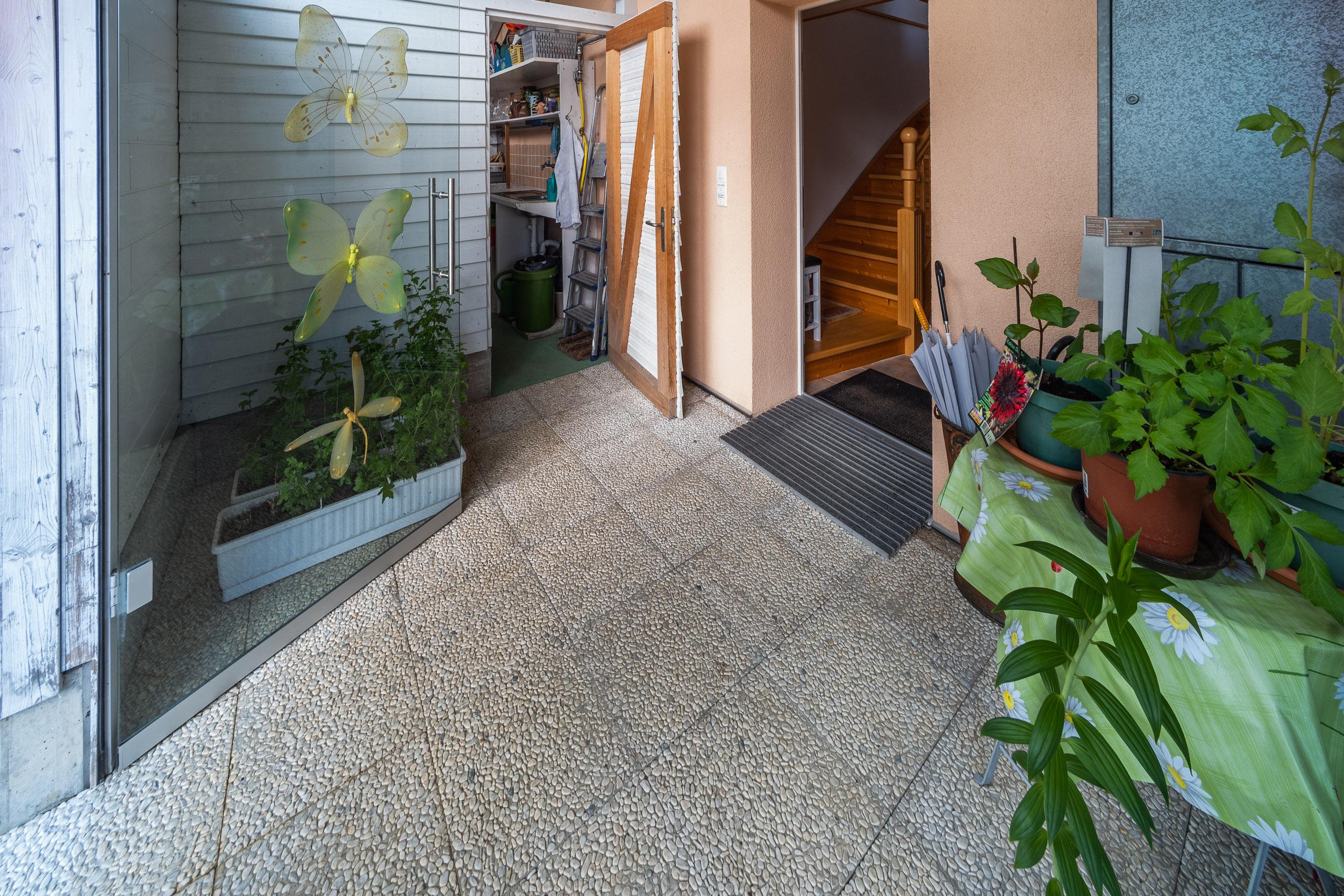 Der Windfang vor der Eingangstür schützt und bietet viel Ablagefläche für Pflanzen und anderes. Links neben der Eingangstür befindet sich ein Raum für Gartengeräte
