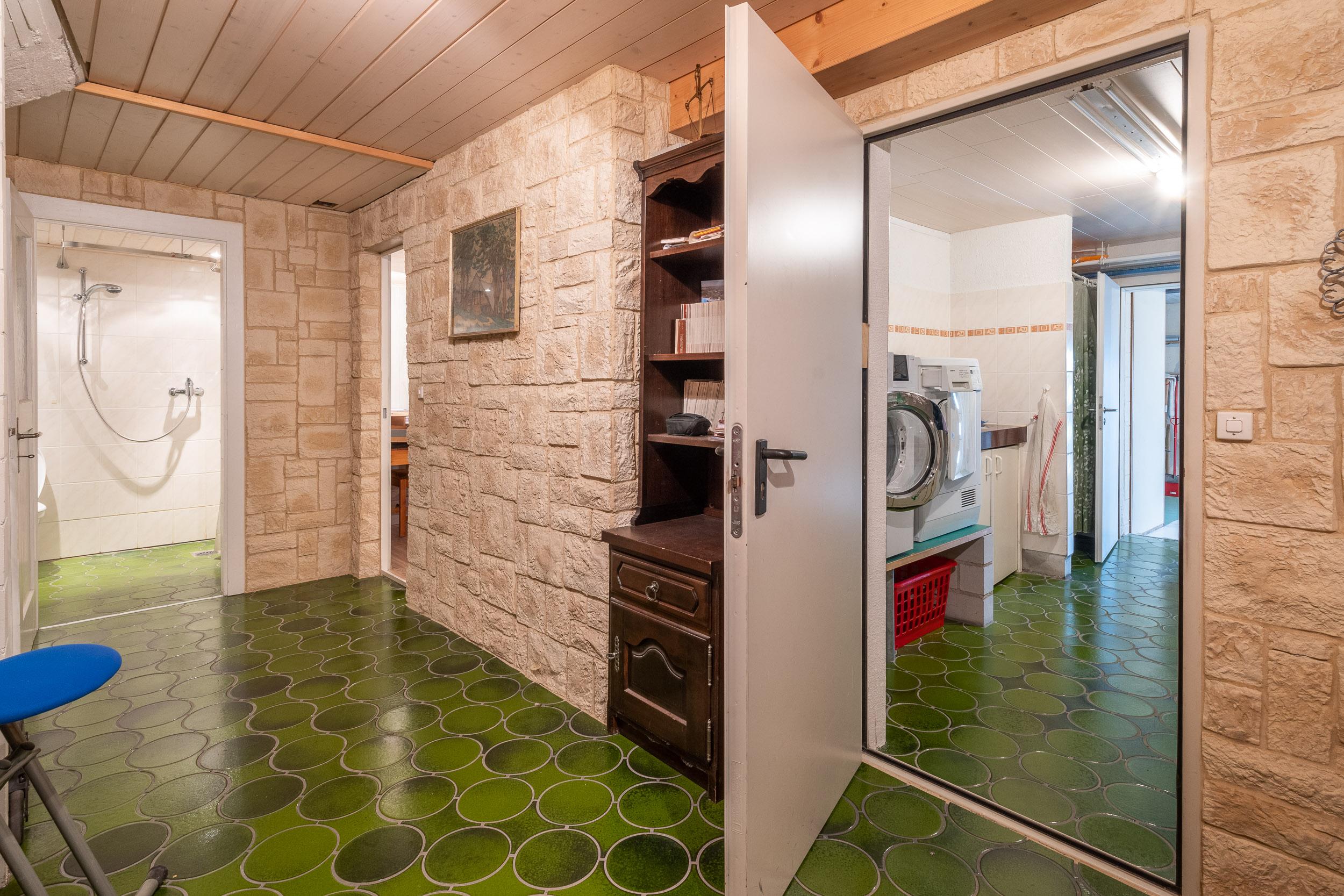Wenn man die Treppe heruntersteigt, gelangt mit in den Keller-Vorraum. Links ein WC/DU, rechts davon der Durchgang in ein kleines Office, hinter dem sich der Naturkeller mit klimatisiertem Weinkeller befindet. Ganz rechts die Waschküche mit Durchgang in den Garten und die Garage
